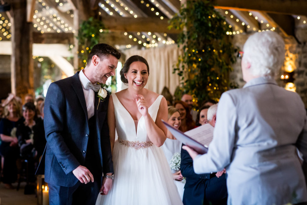 Tithe Barn Wedding Photography - Couple laughing during the ceremony