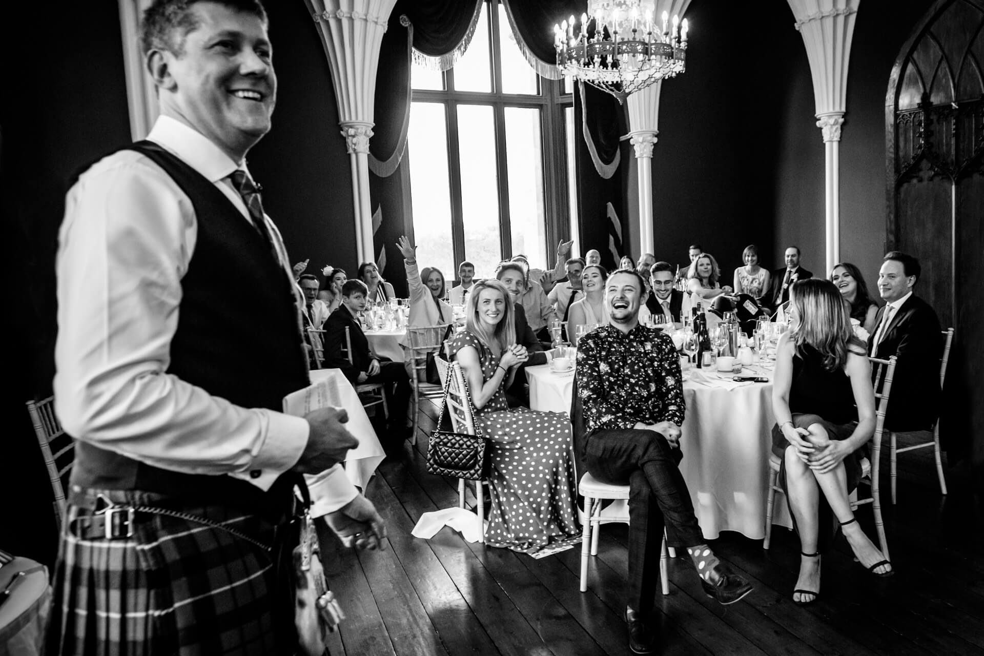 wedding guests laughing during the grooms speech