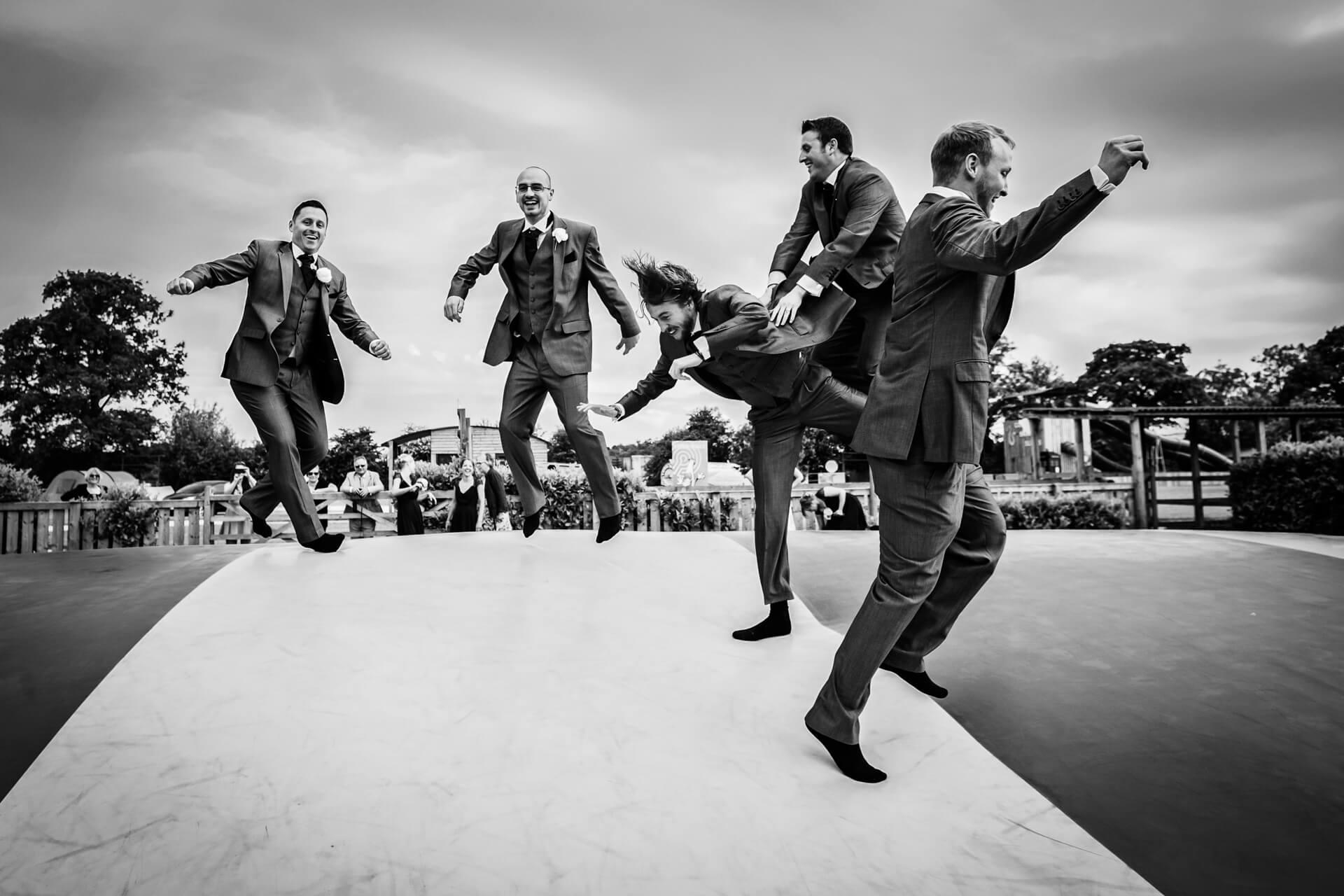 groomsmen bouncing on a bouncy platform