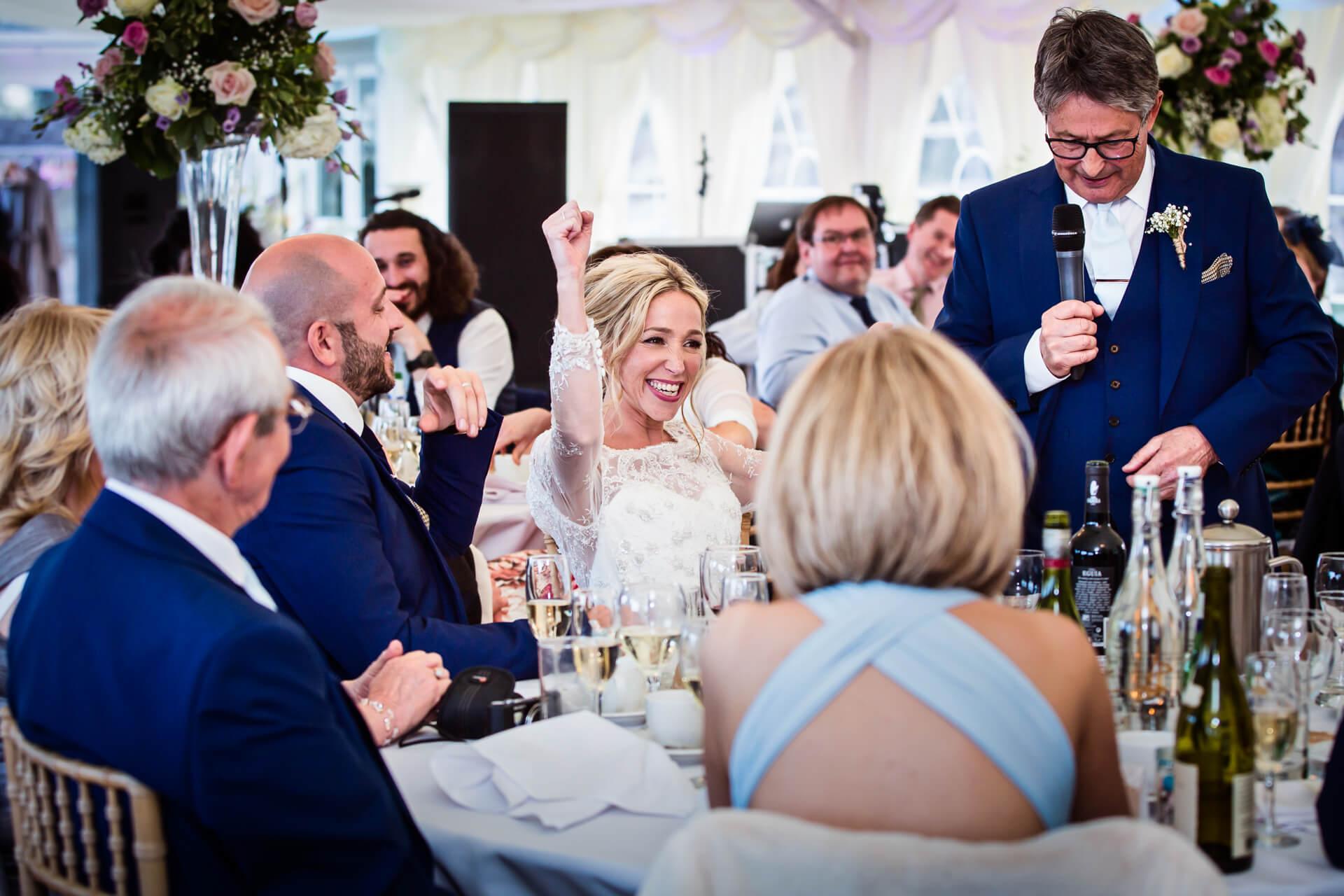 bride cheering during her fathers wedding speech