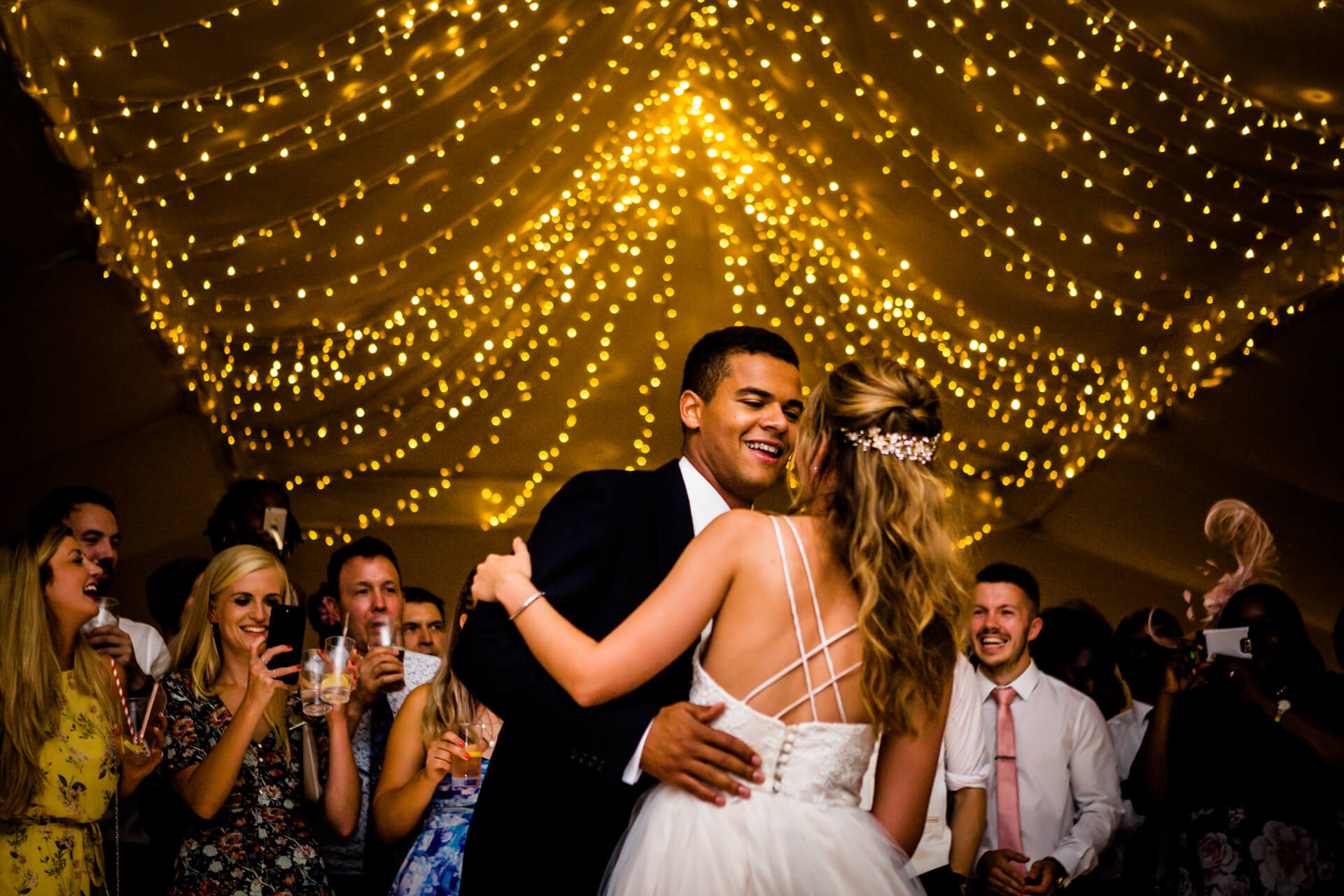bride and groom dancing under some fairy lights