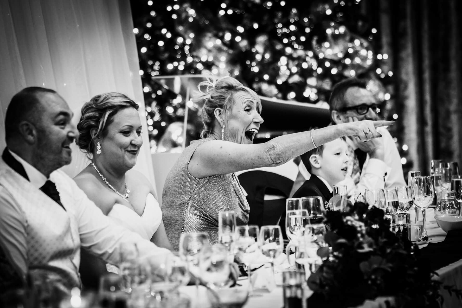 mother of the bride pointing and laughing