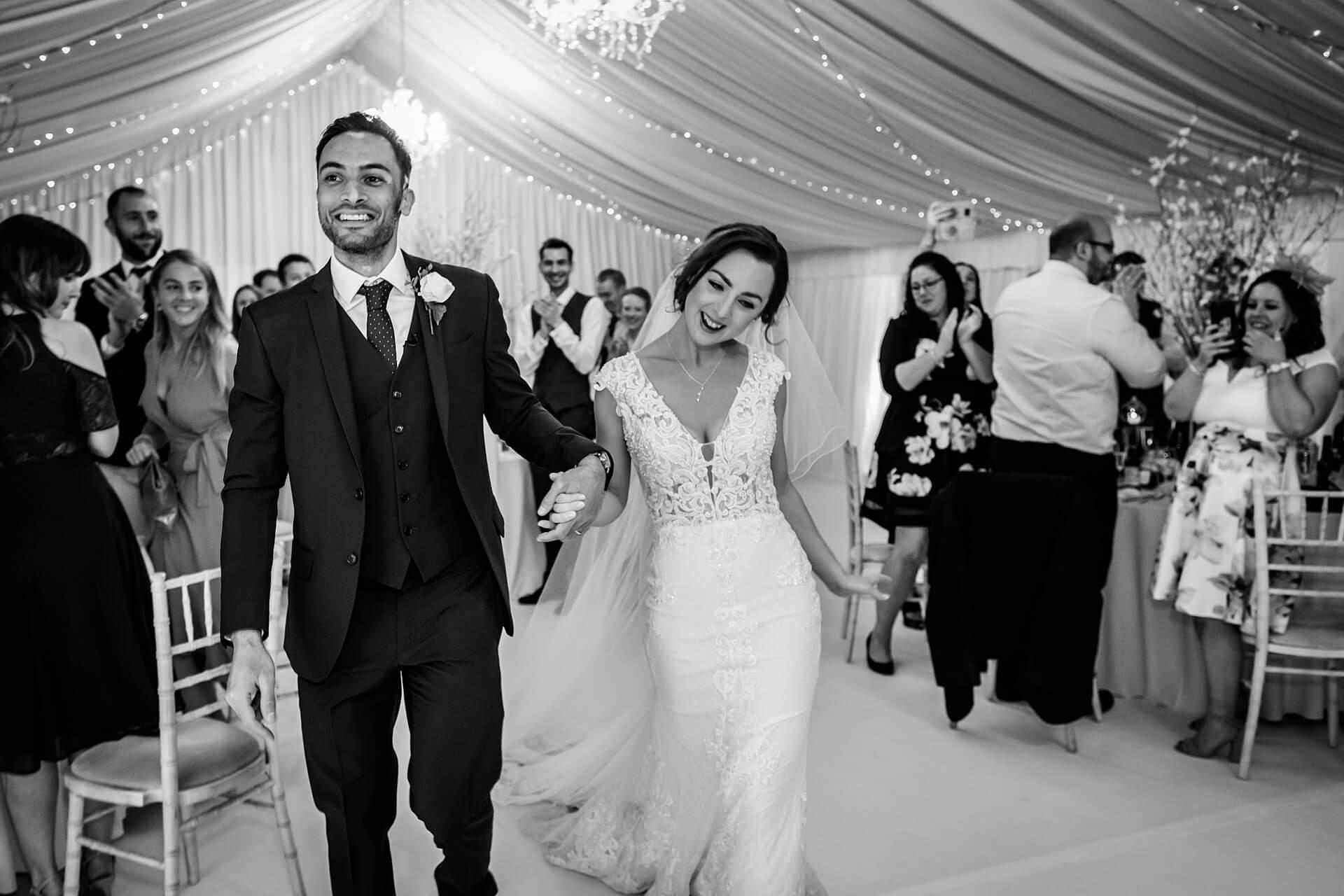 bride and groom walking into the wedding breakfast room to lots of cheers