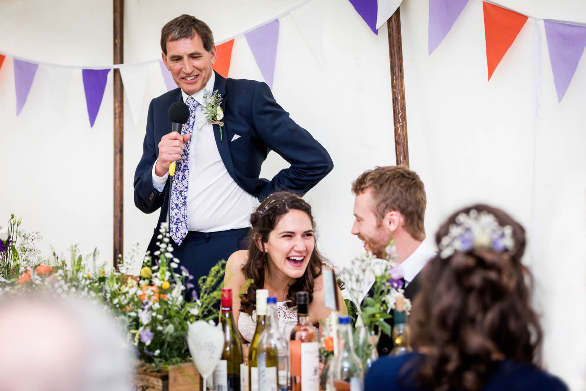 bride laughing at the groom whilst her father delivers his speech
