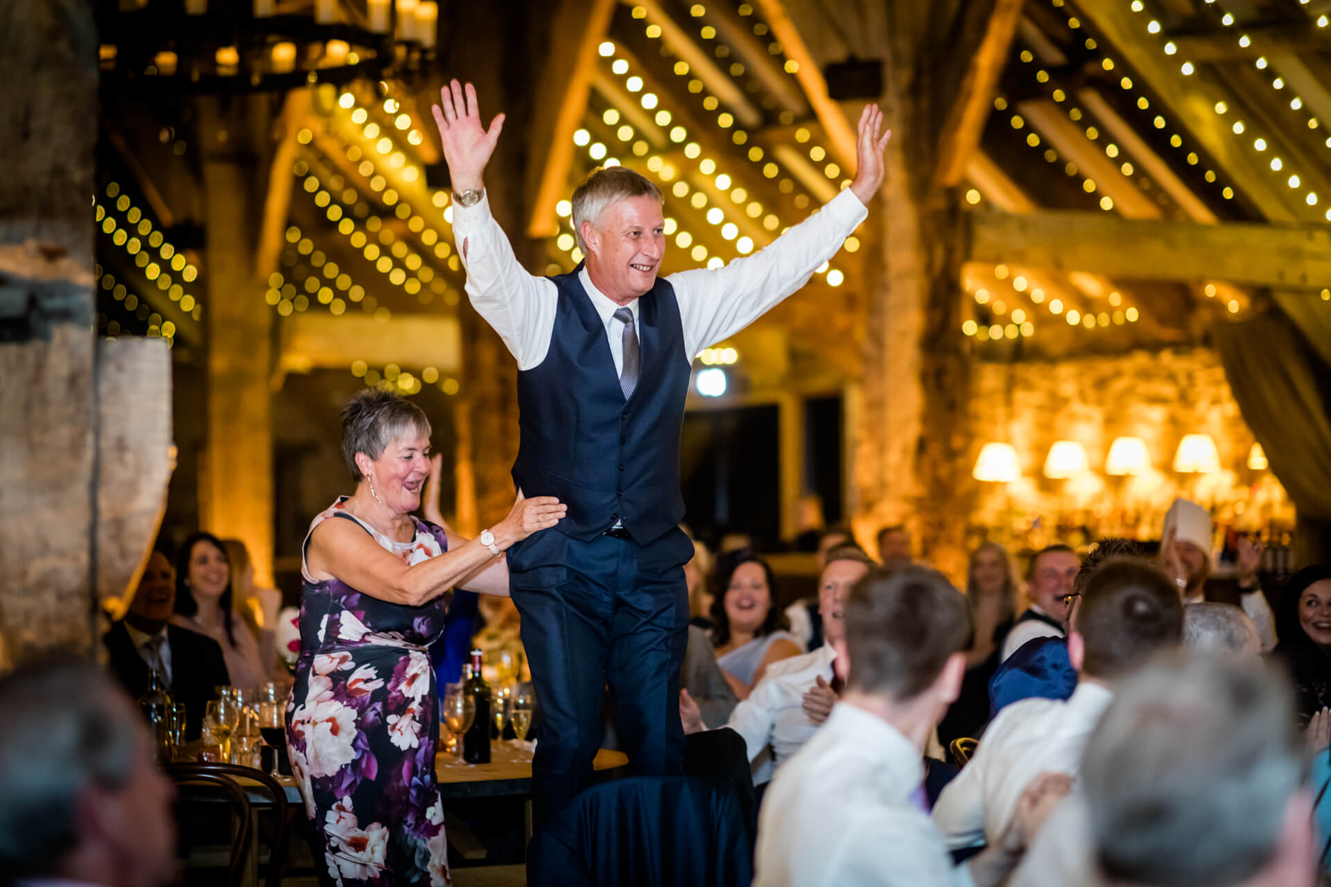 one of the wedding guests standing on a chair and cheering during the speeches