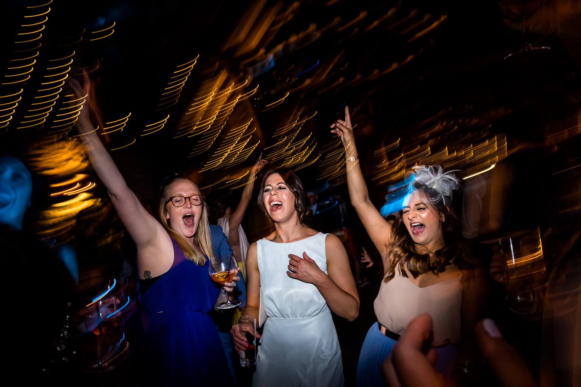 three wedding guests on the dance floor