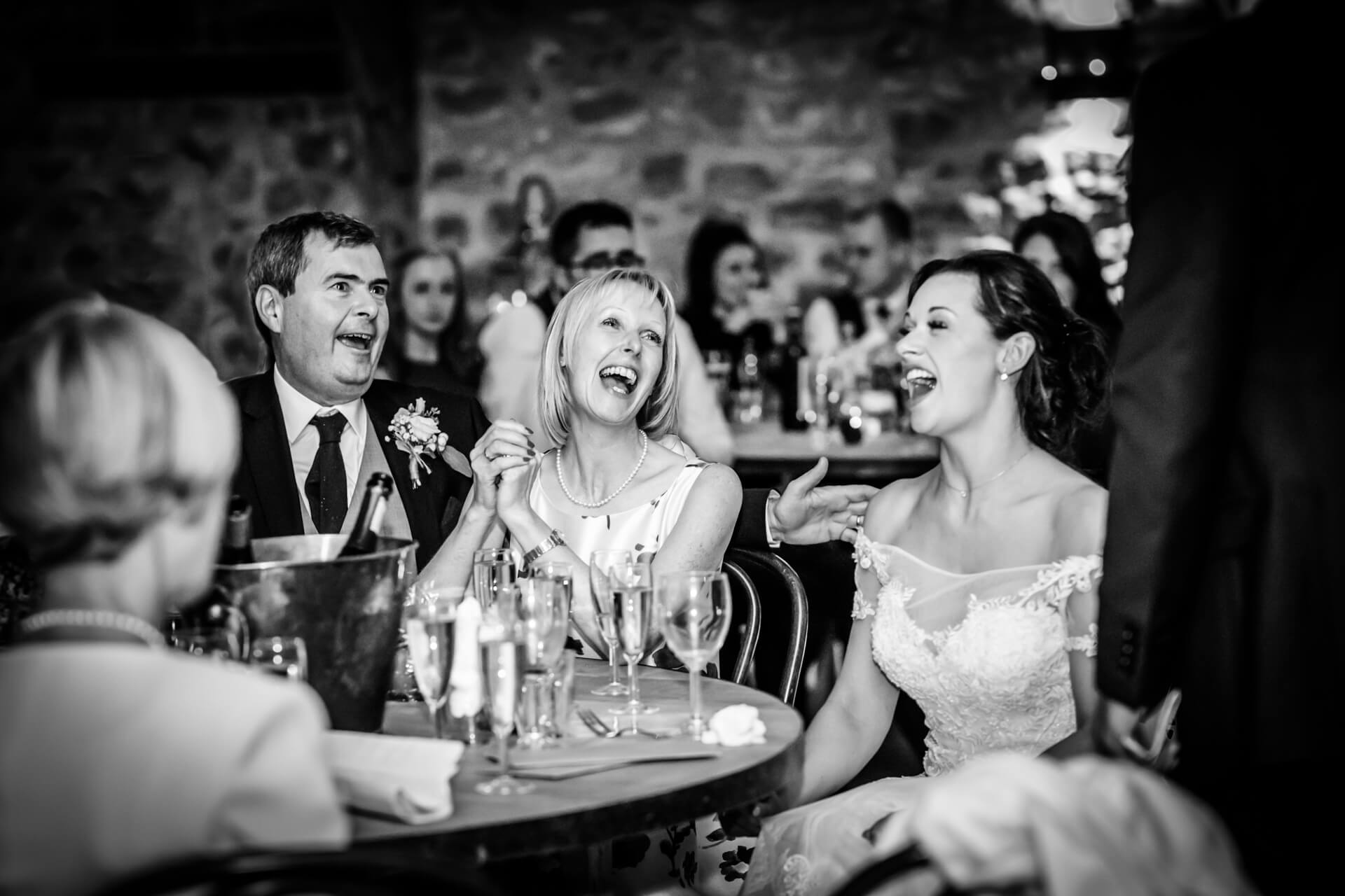 bride laughing with her mum and dad during the speeches
