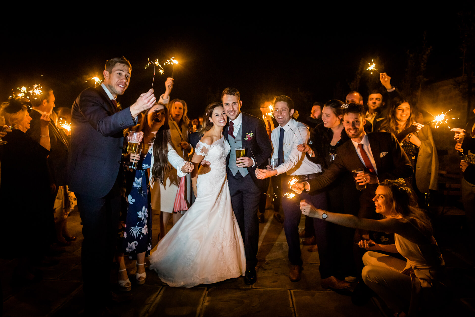 bride and groom surrounded by guests holding sparklers