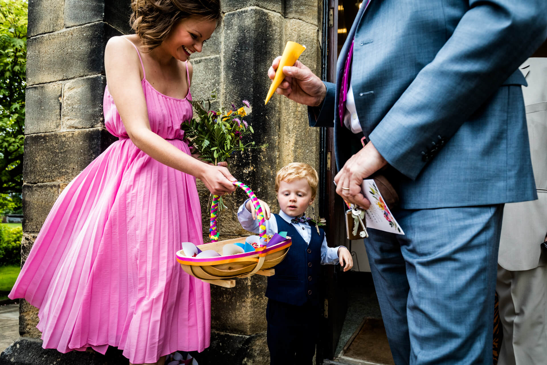 little pageboy picks a confetti cone out of the basket