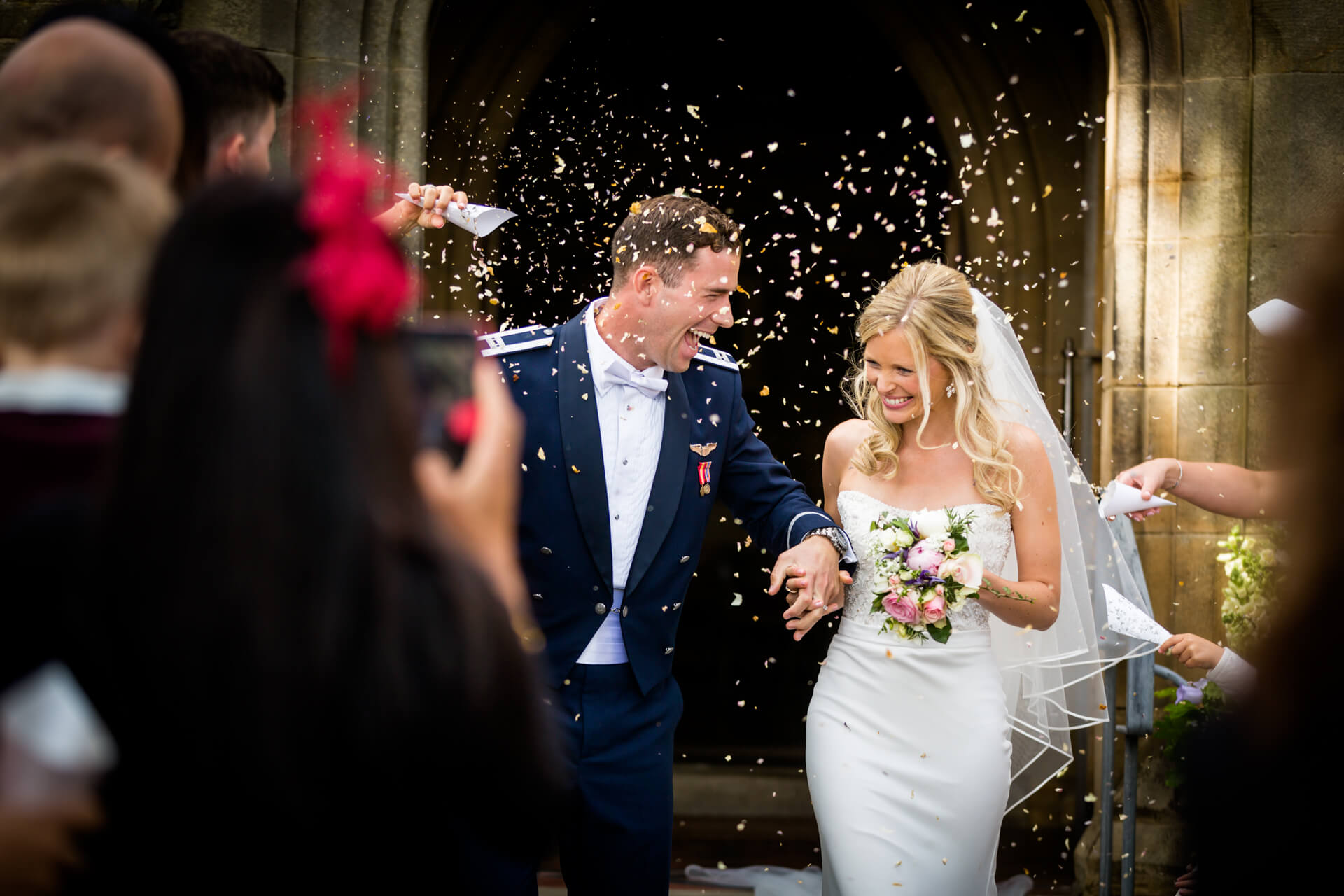 wedding couple laugh at each other whist run-in under the confetti