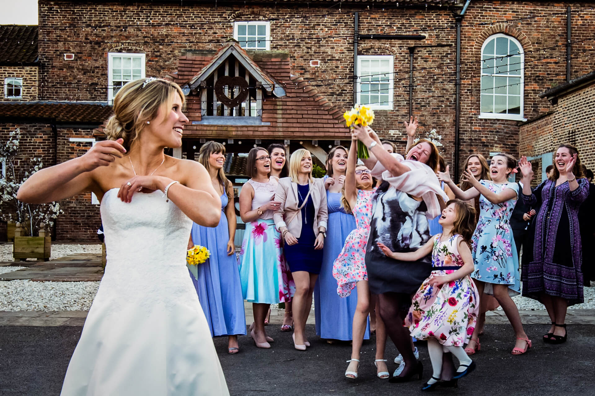 guest jumps to catch the wedding bouquet which is thrown by the bride at Hornington Manor