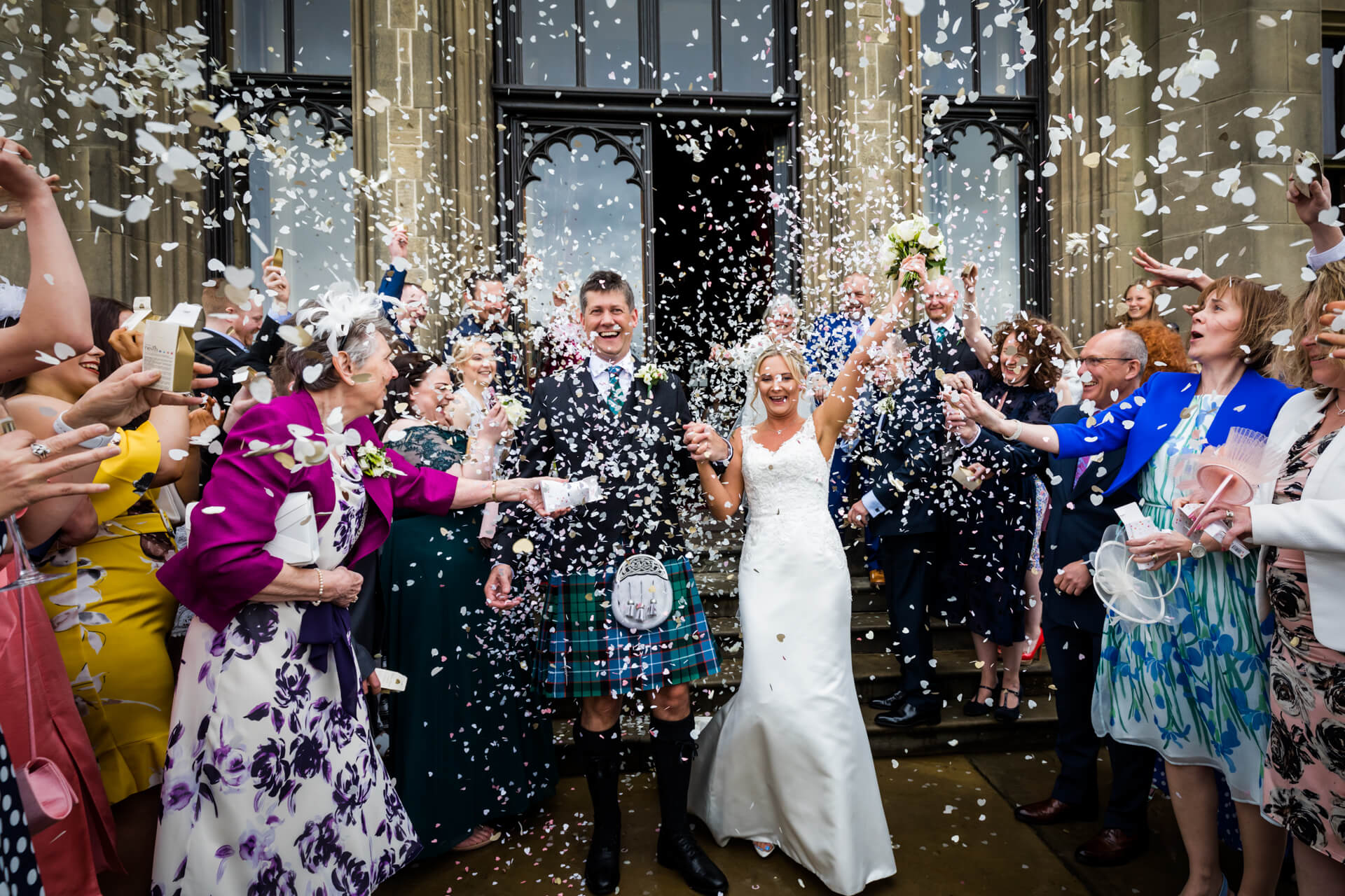 wedding couple under a dense shower of confetti at Allerton Castle