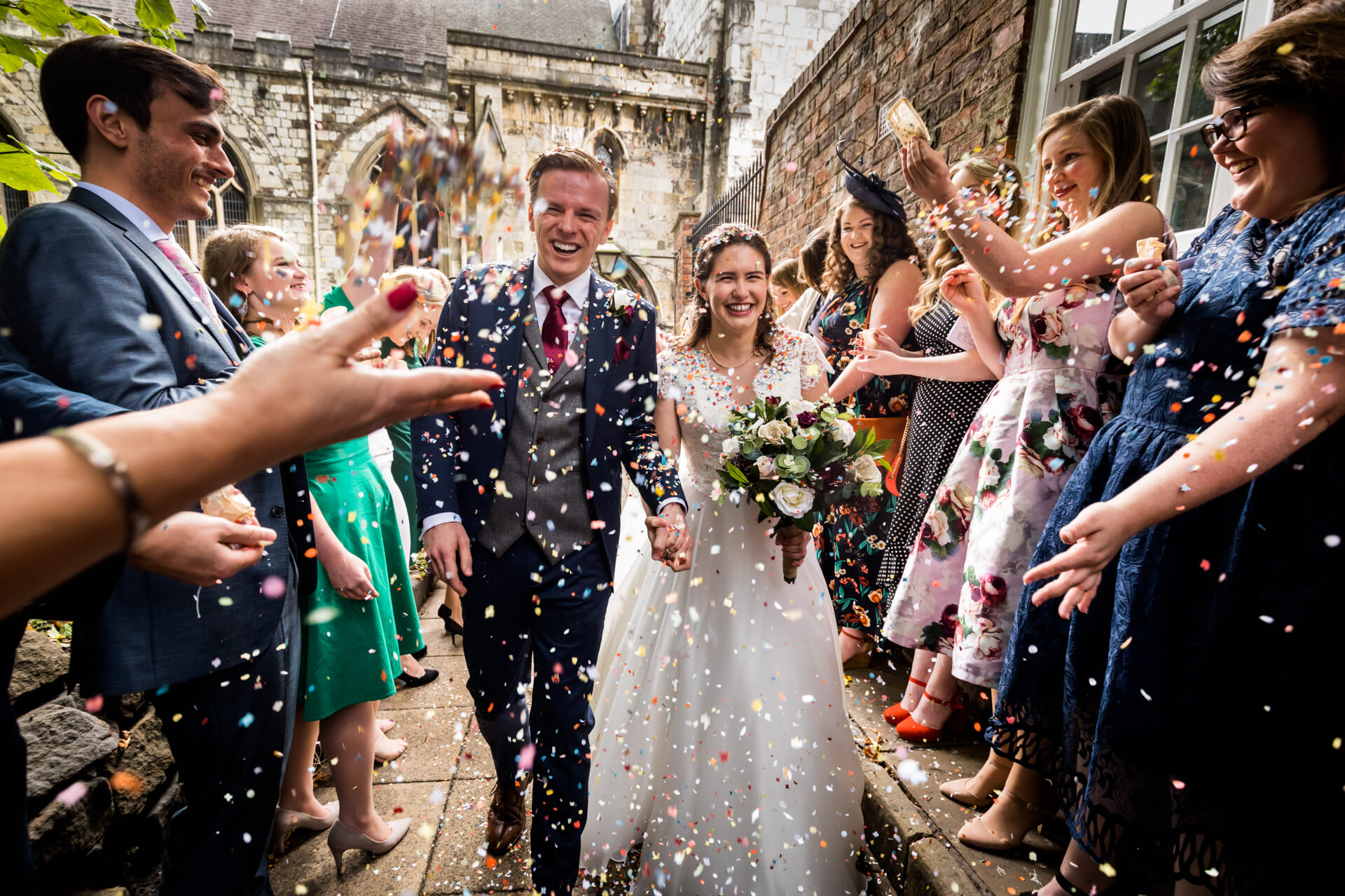 bride and groom run through the confetti shower in York