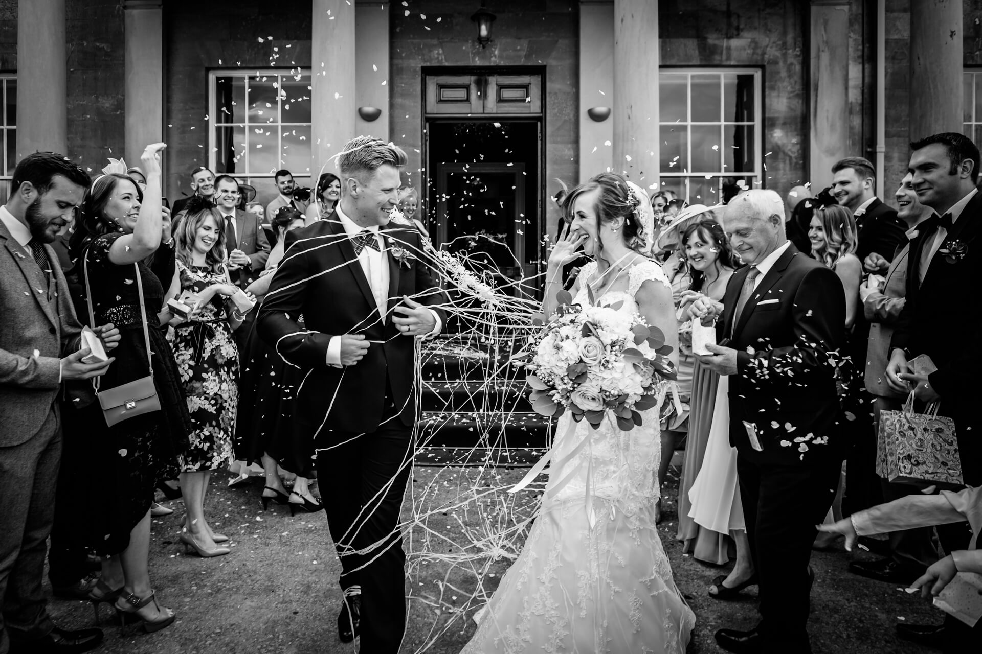 bride and groom are showered with confetti string at Rudding park