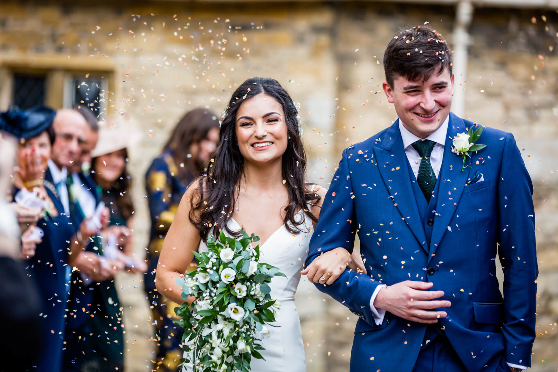 bride and groom smiling as they walk through a confetti shower