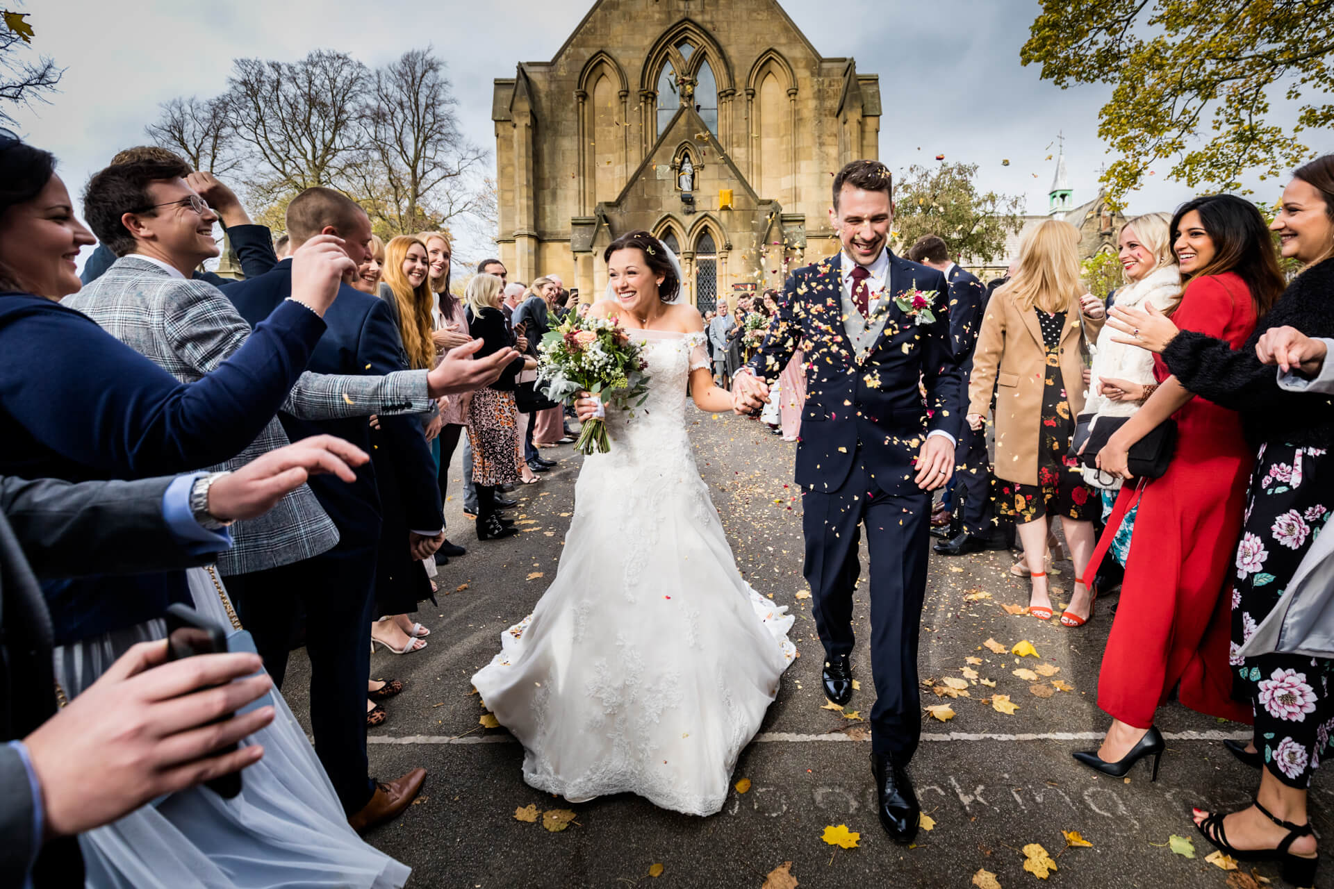 couple walking thorugh the confetti line at a church in Skipton