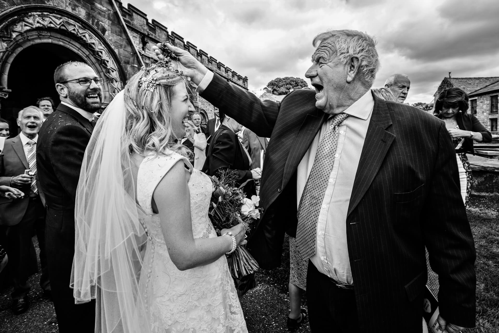 bride laughs as her uncle throws confetti over her