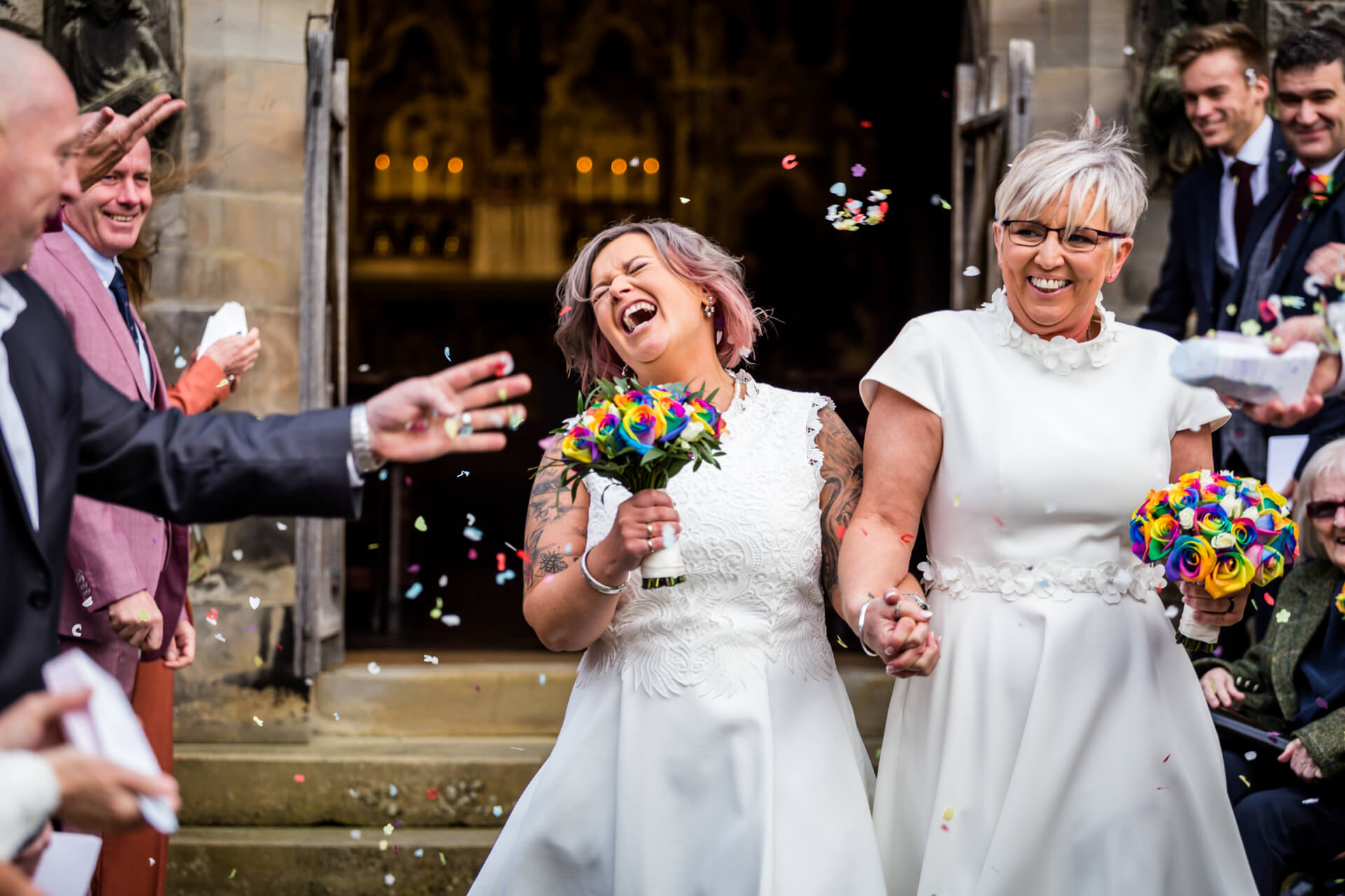 the couple laugh as confetti is thrown over them