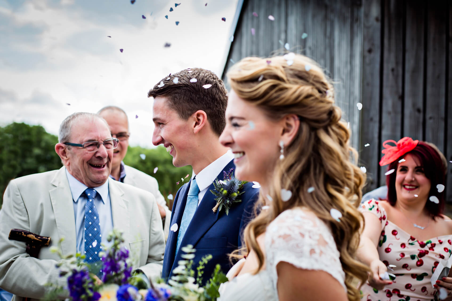 guests smile at the wedding couple as they throw confetti