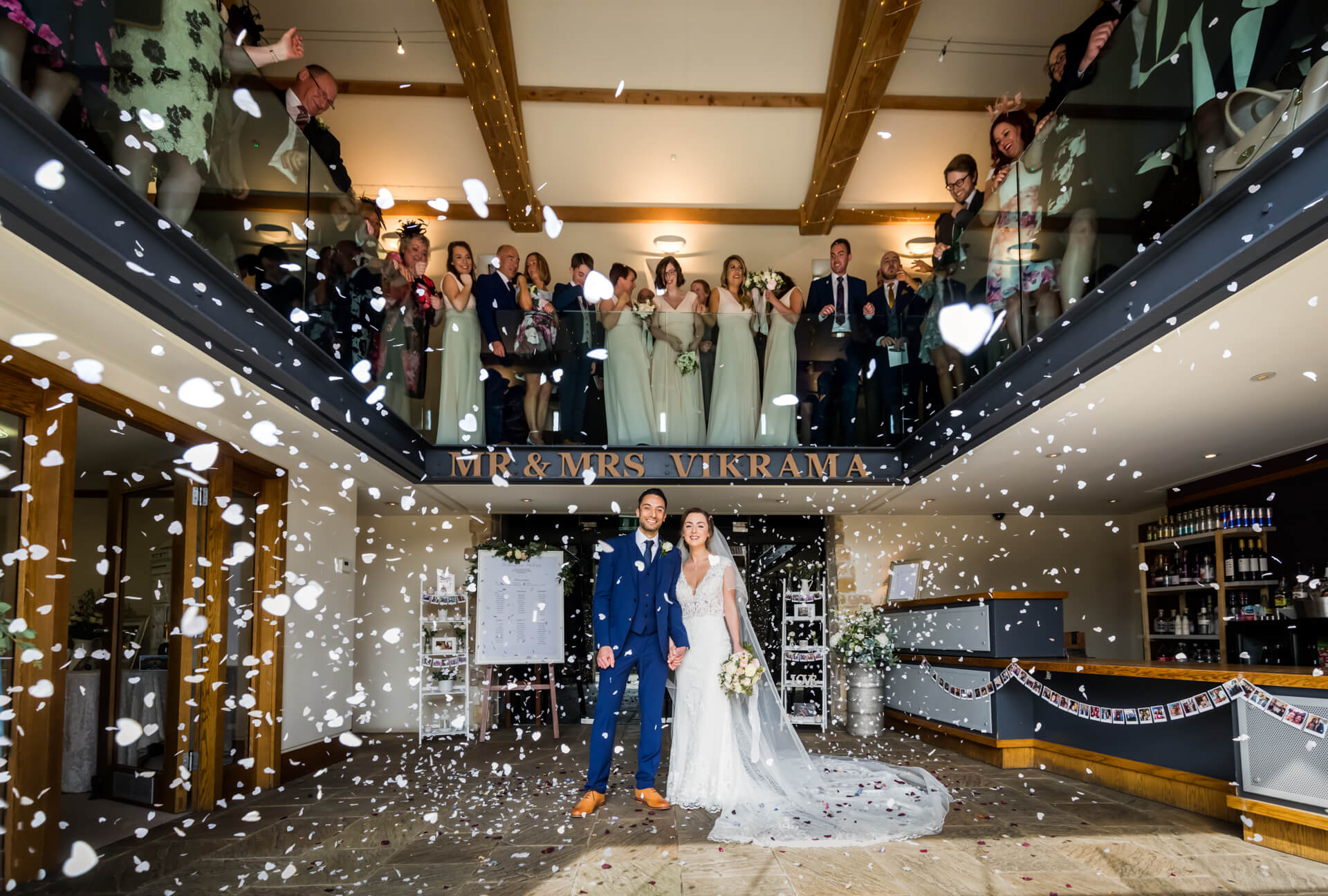 guests throw confetti down onto the couple from a balcony