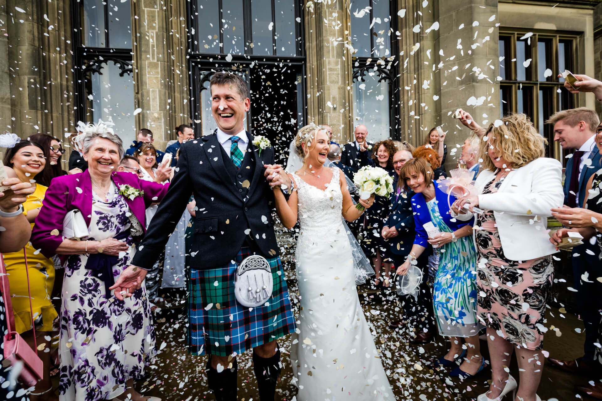 bride and groom are showered with confetti on the Allerton Castle steps