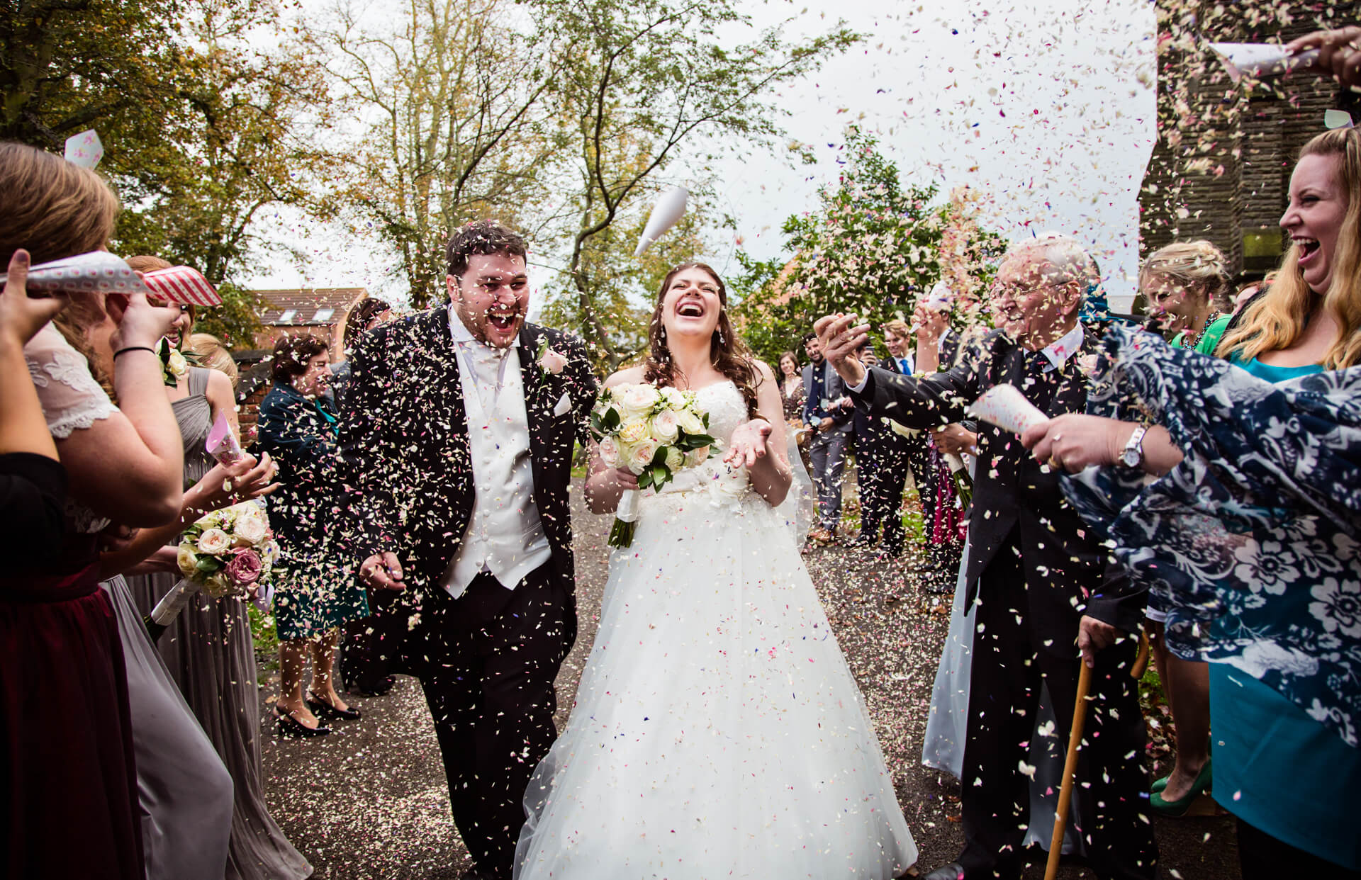 wedding couple being bombarded with a tune of confetti