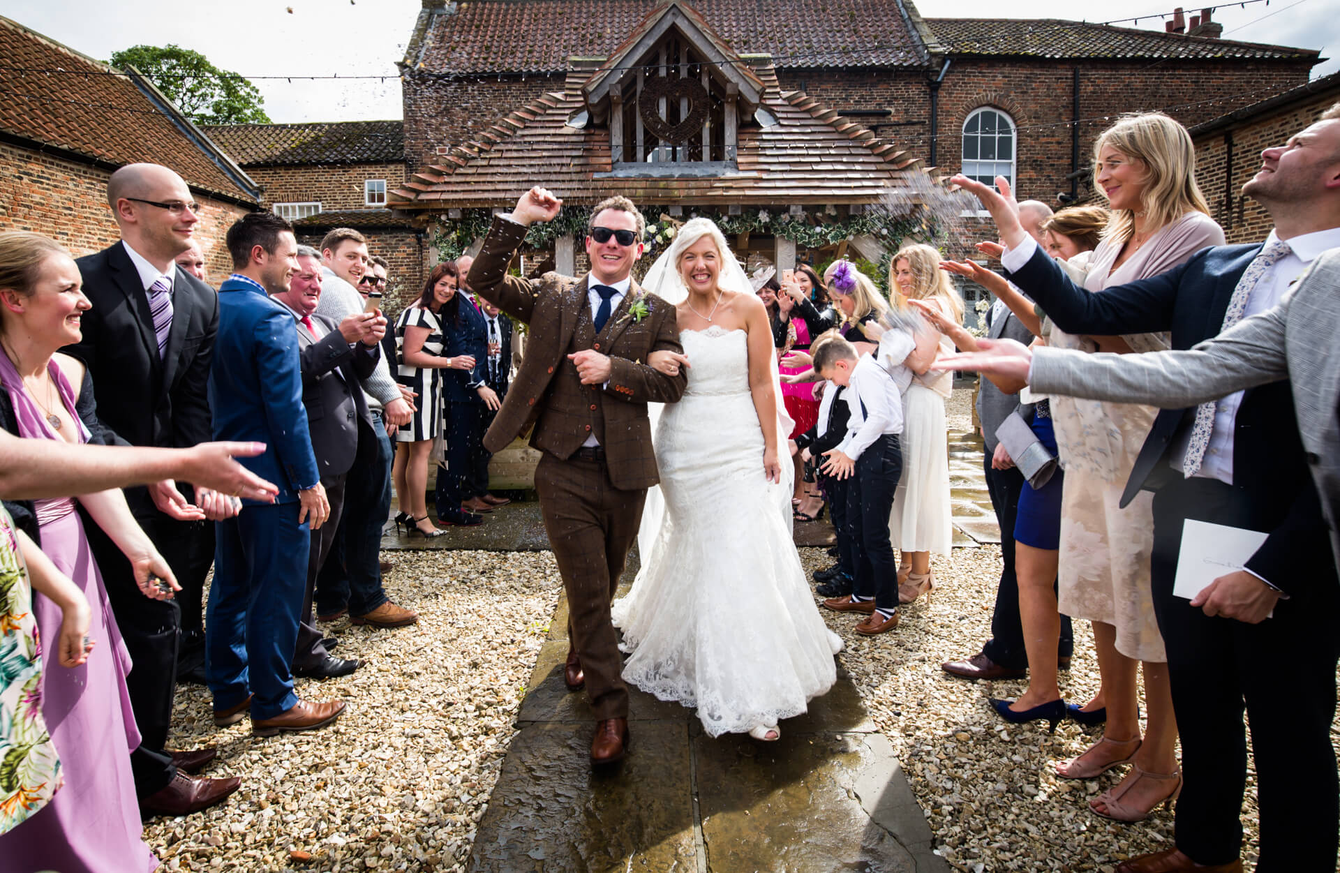 couple walking through a crowd of confetti throwers at Hornington Manor