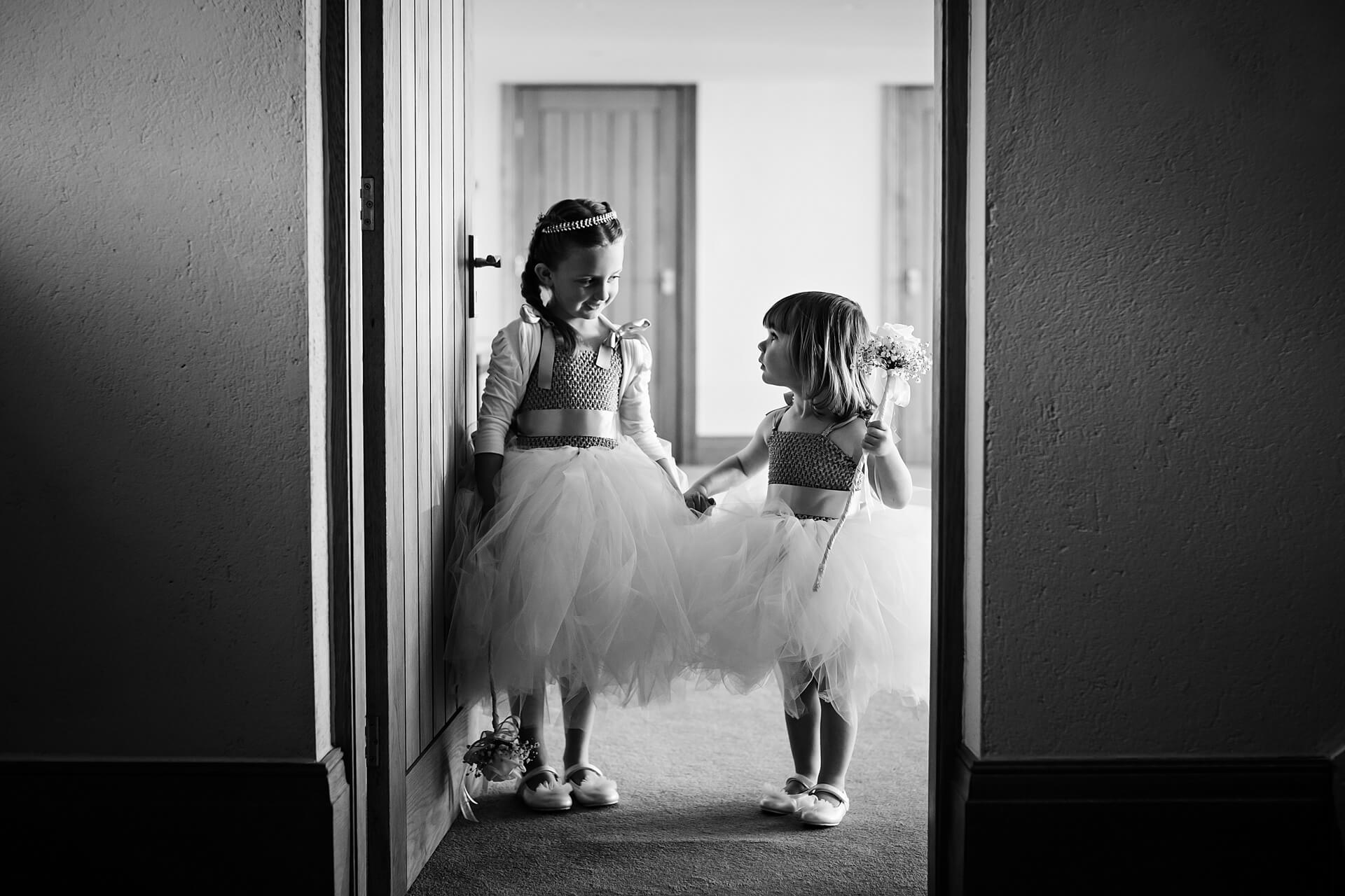 two flower girls holding hands and smiling in a doorway