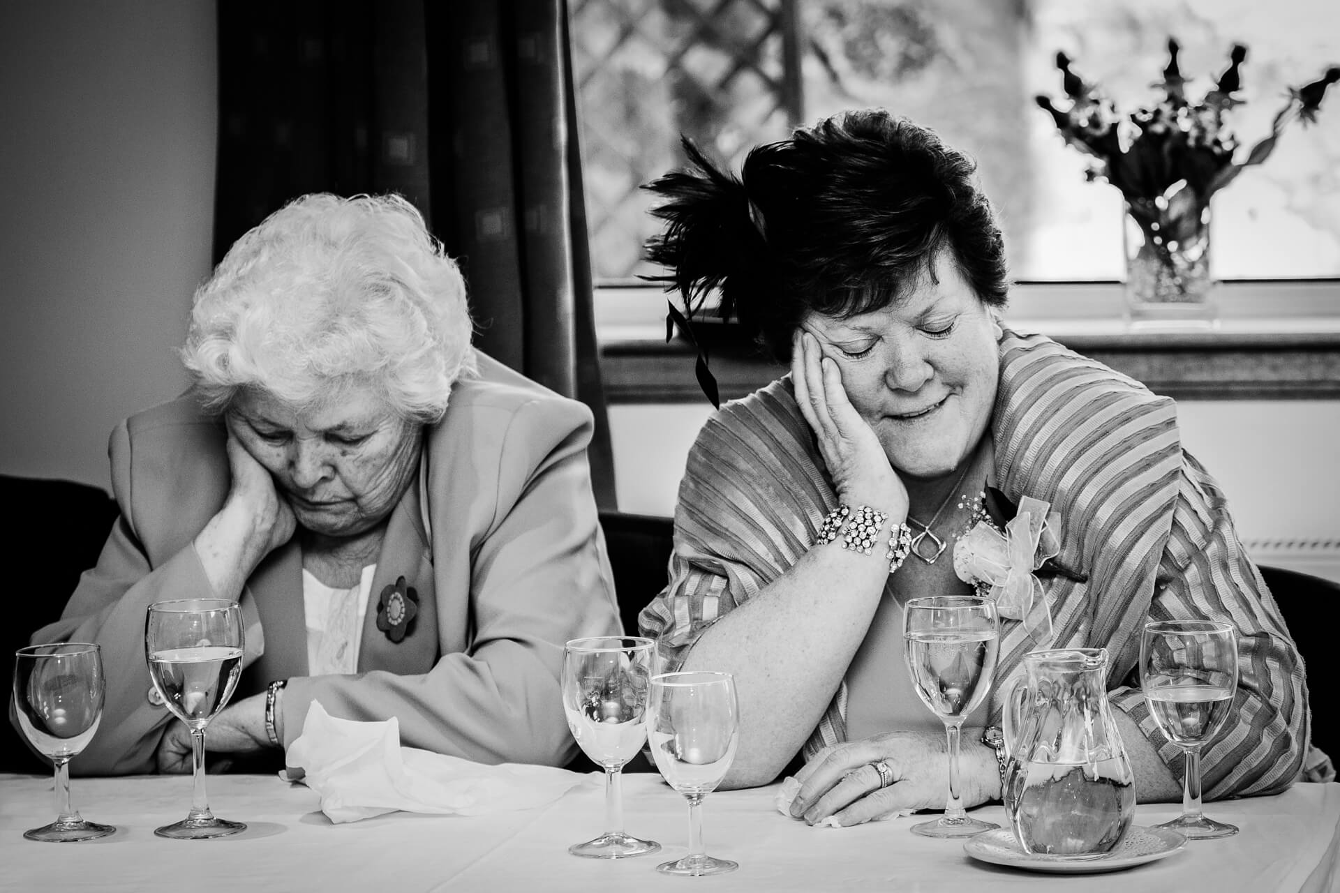 two grandmas sleeping during the wedding speeches