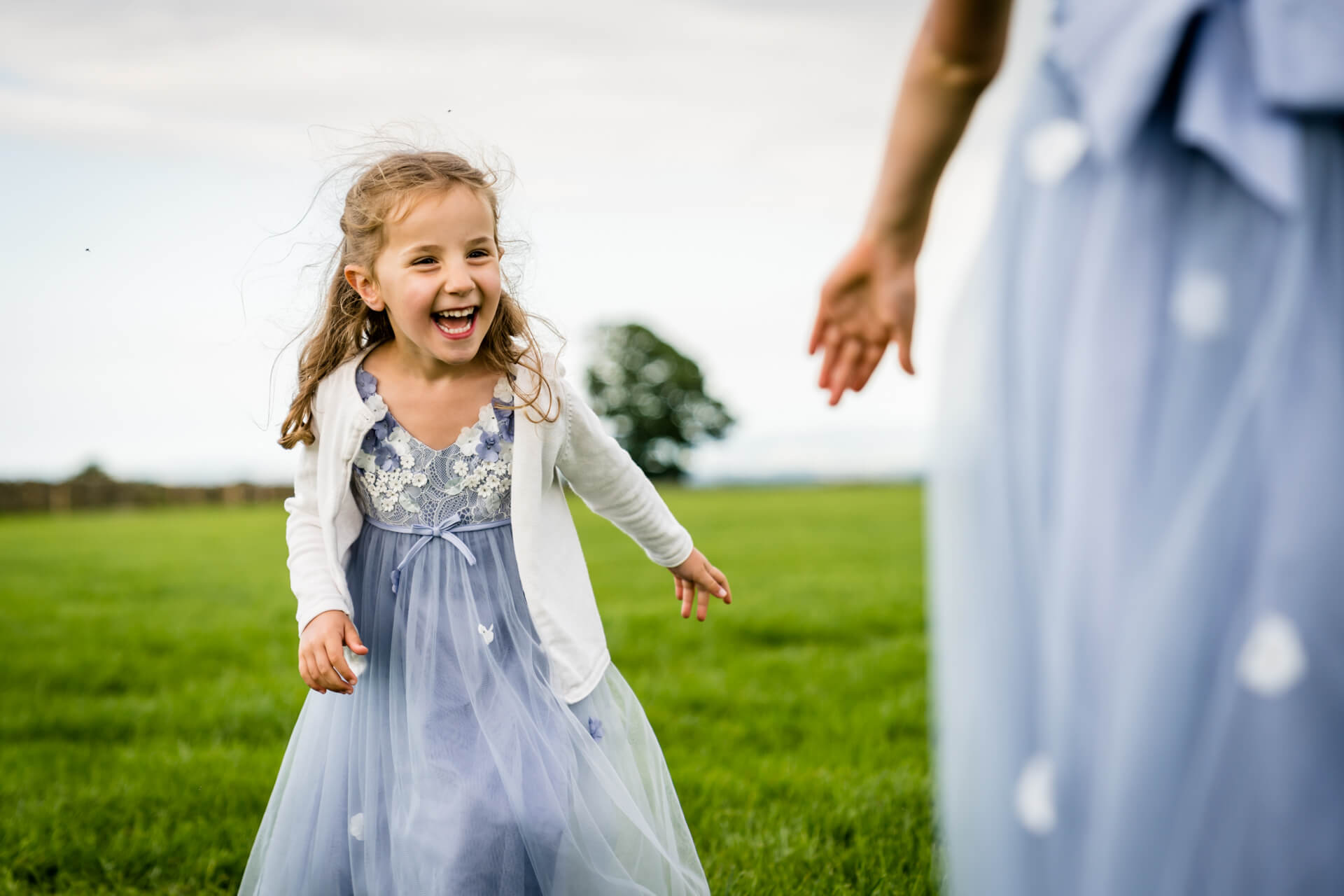 flower girl running after her sister in a field
