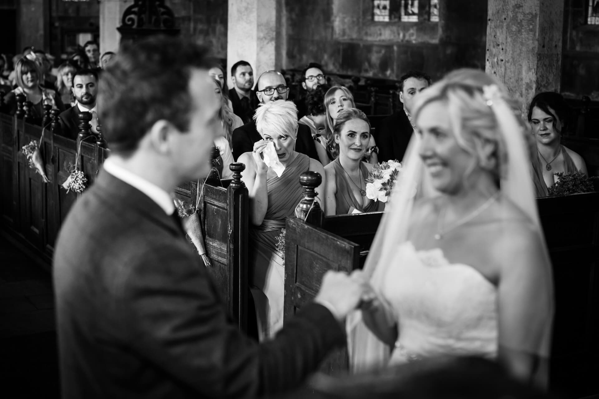 bridesmaid crying into her handkerchief whilst the couple say their wedding vows