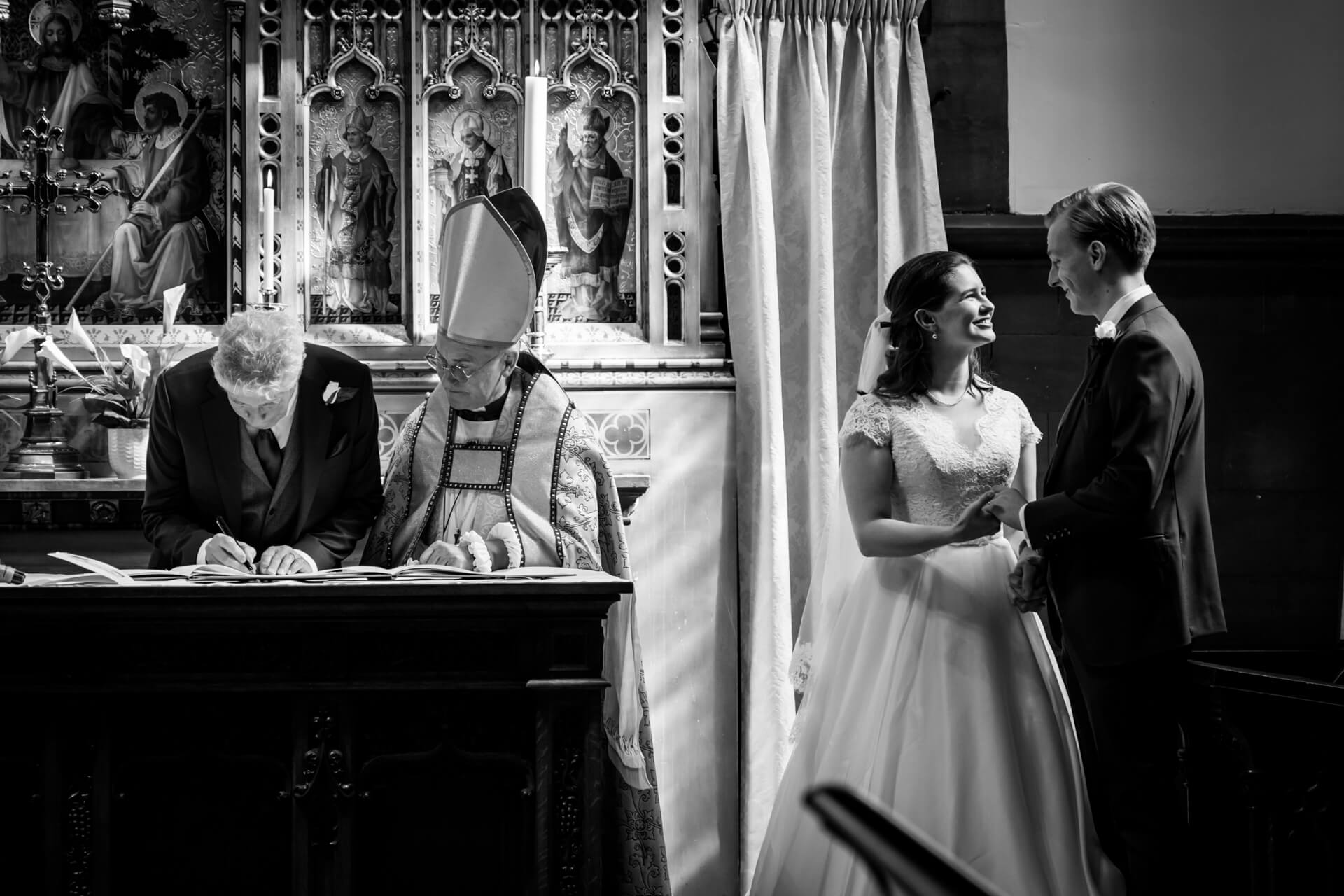 wedding couple wait in the church whilst the father of the bride signs the registry