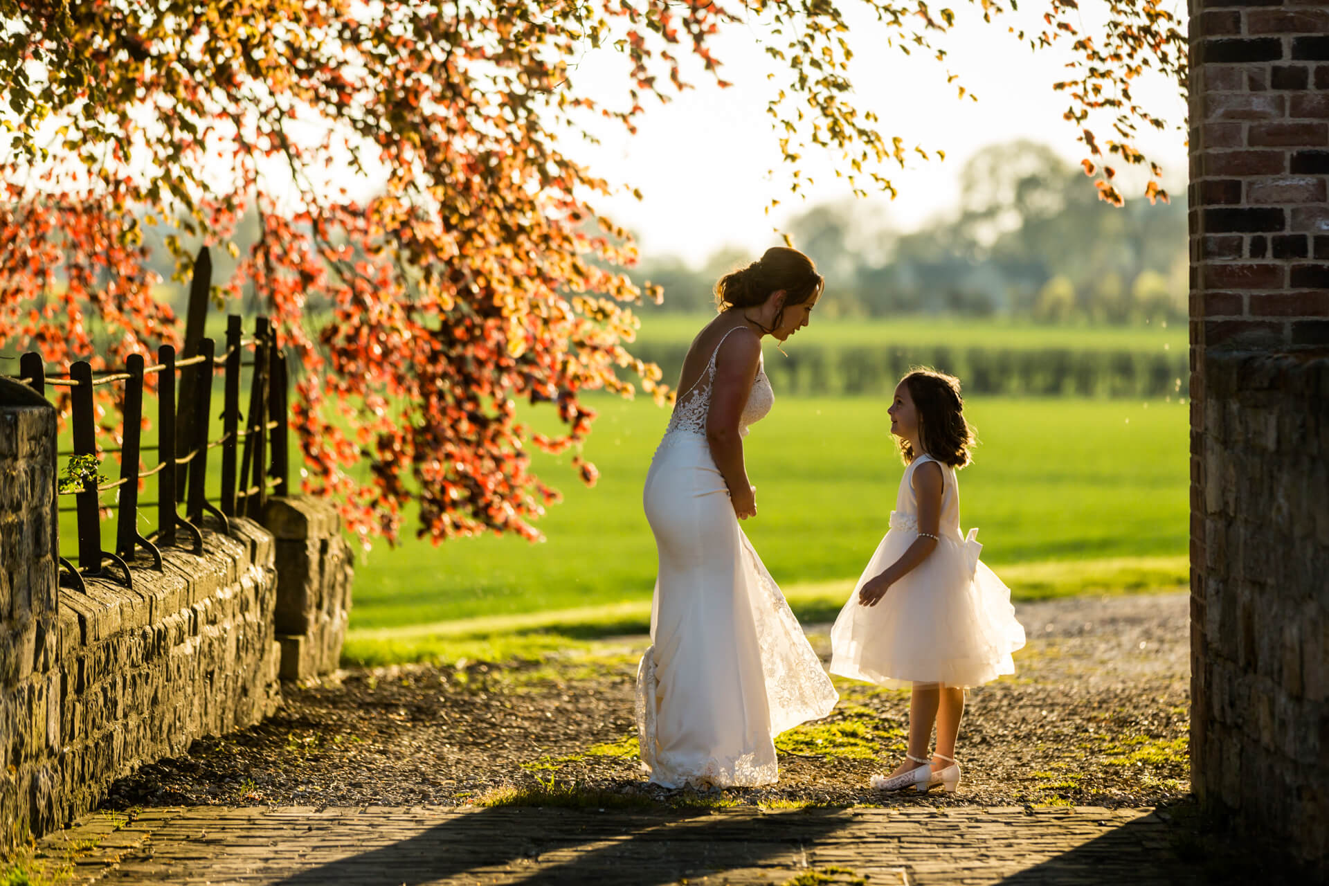 bride and flower girl chatting together in some beautiful sunlight