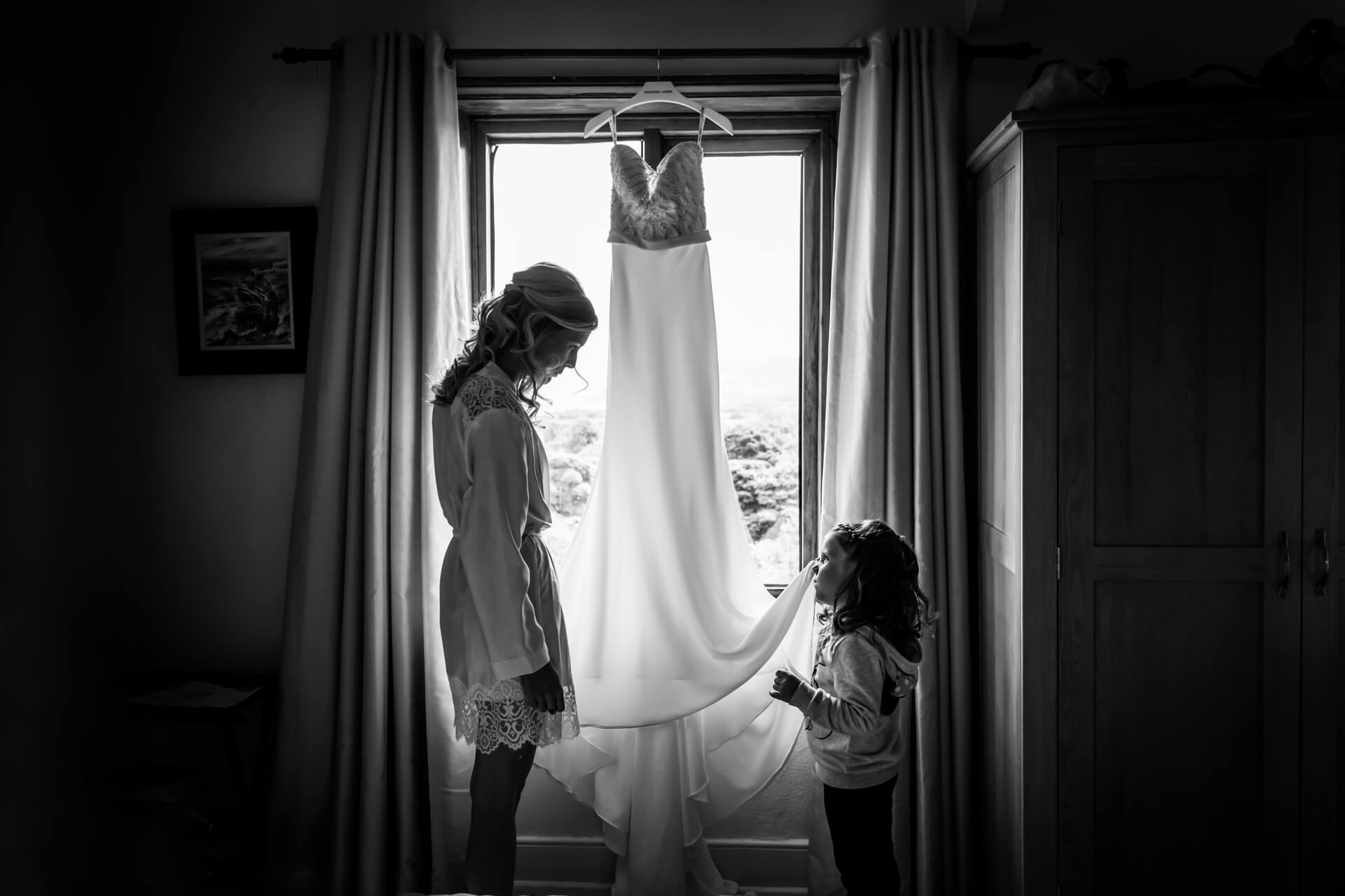 flower girl holding the brides dress in from of a window and talking to the bride