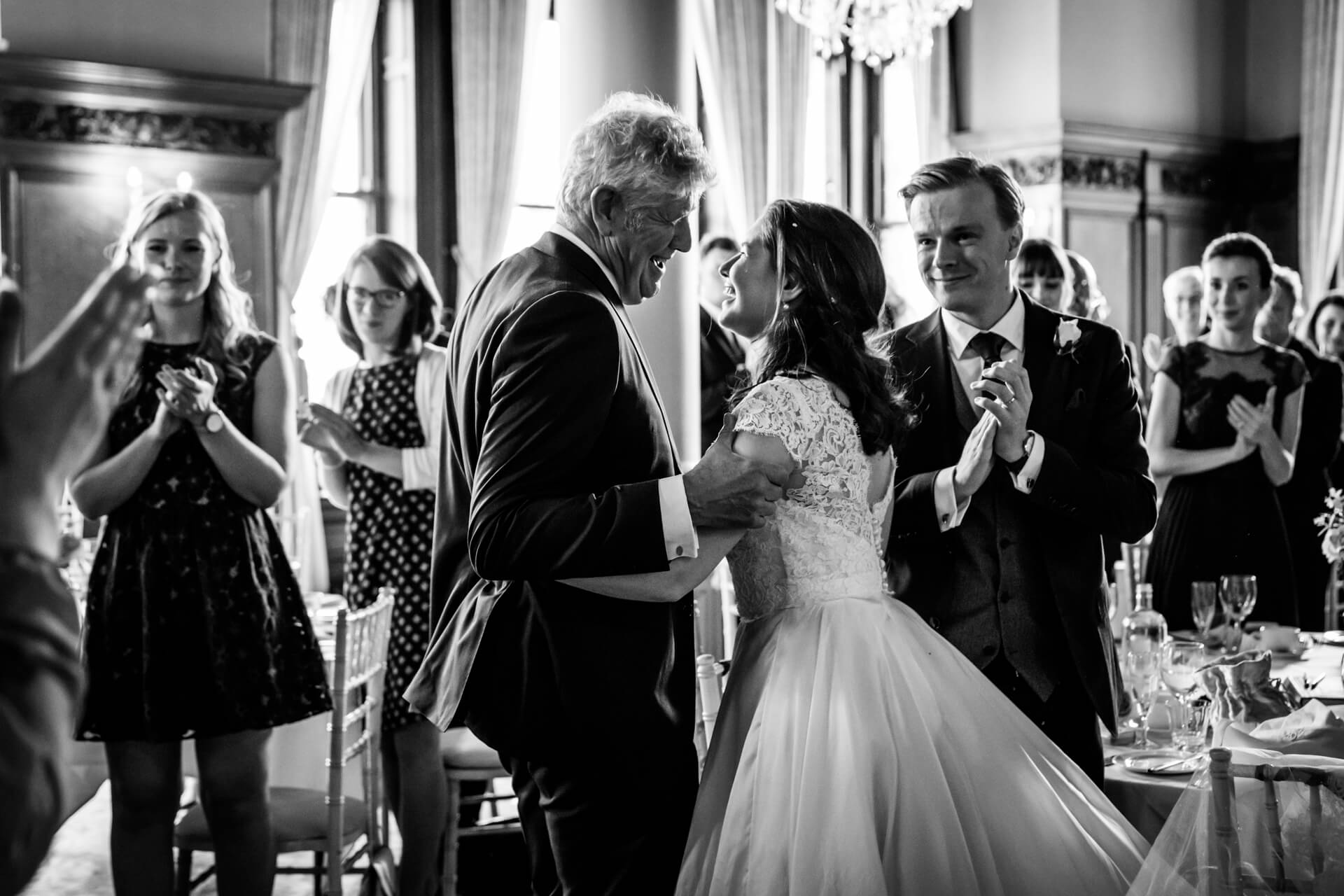 bride and her father laughing together as all the wedding guests clap