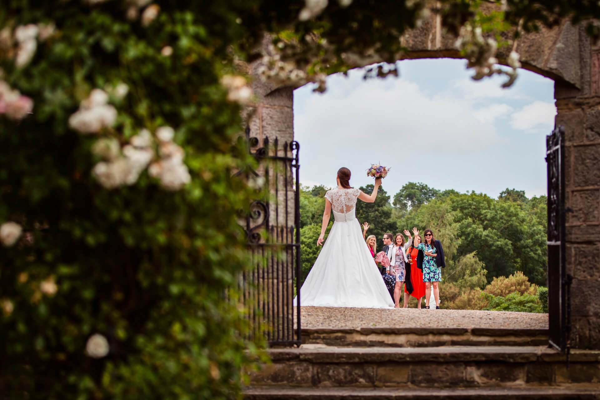 bride waving to the guests with her bouquet at Woodhall hotel
