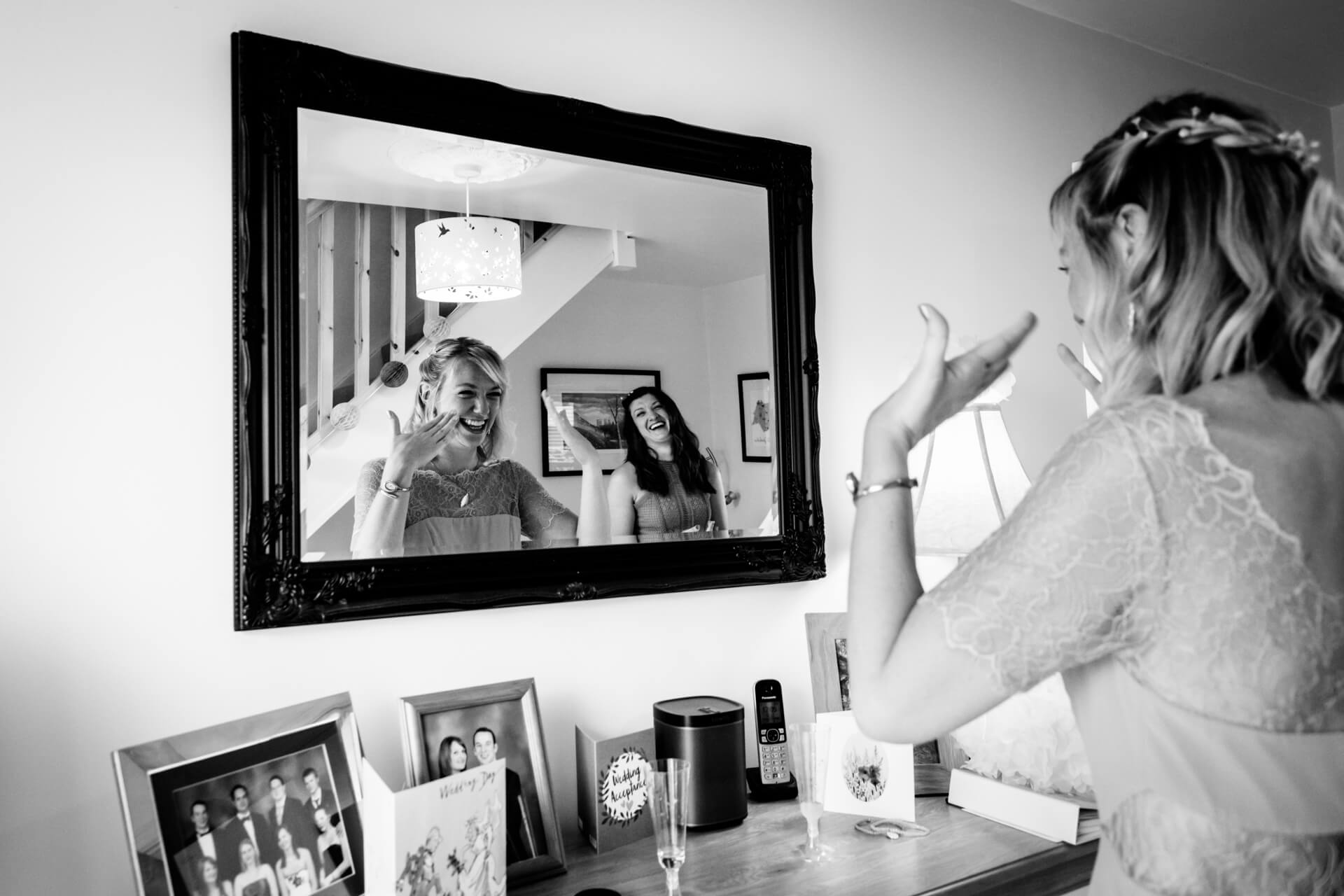 bride and bridesmaid looking in the mirror and laughing