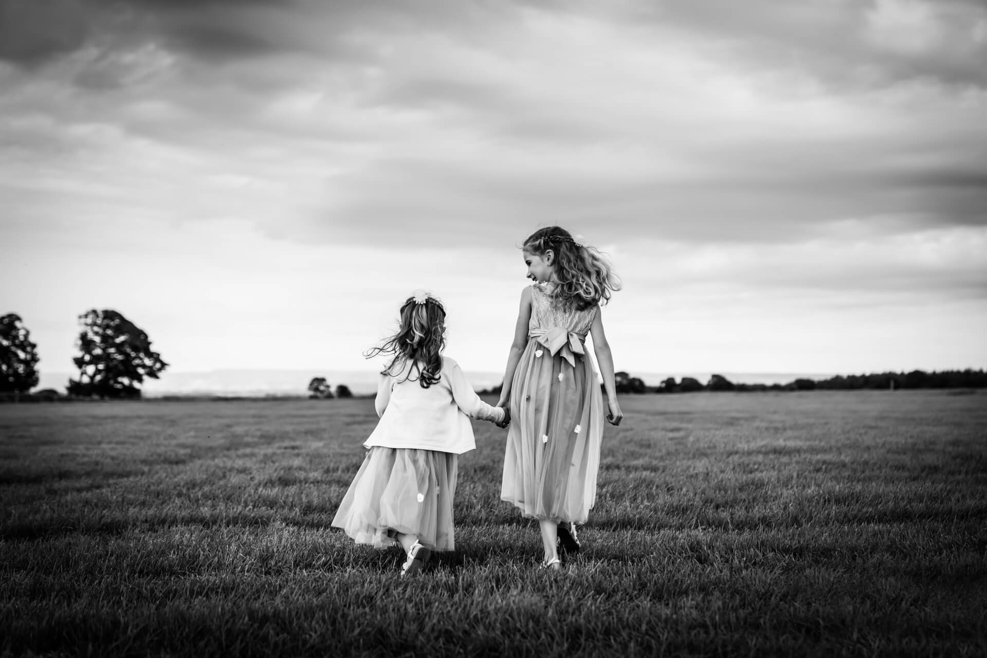 two flower girls walking together in a field