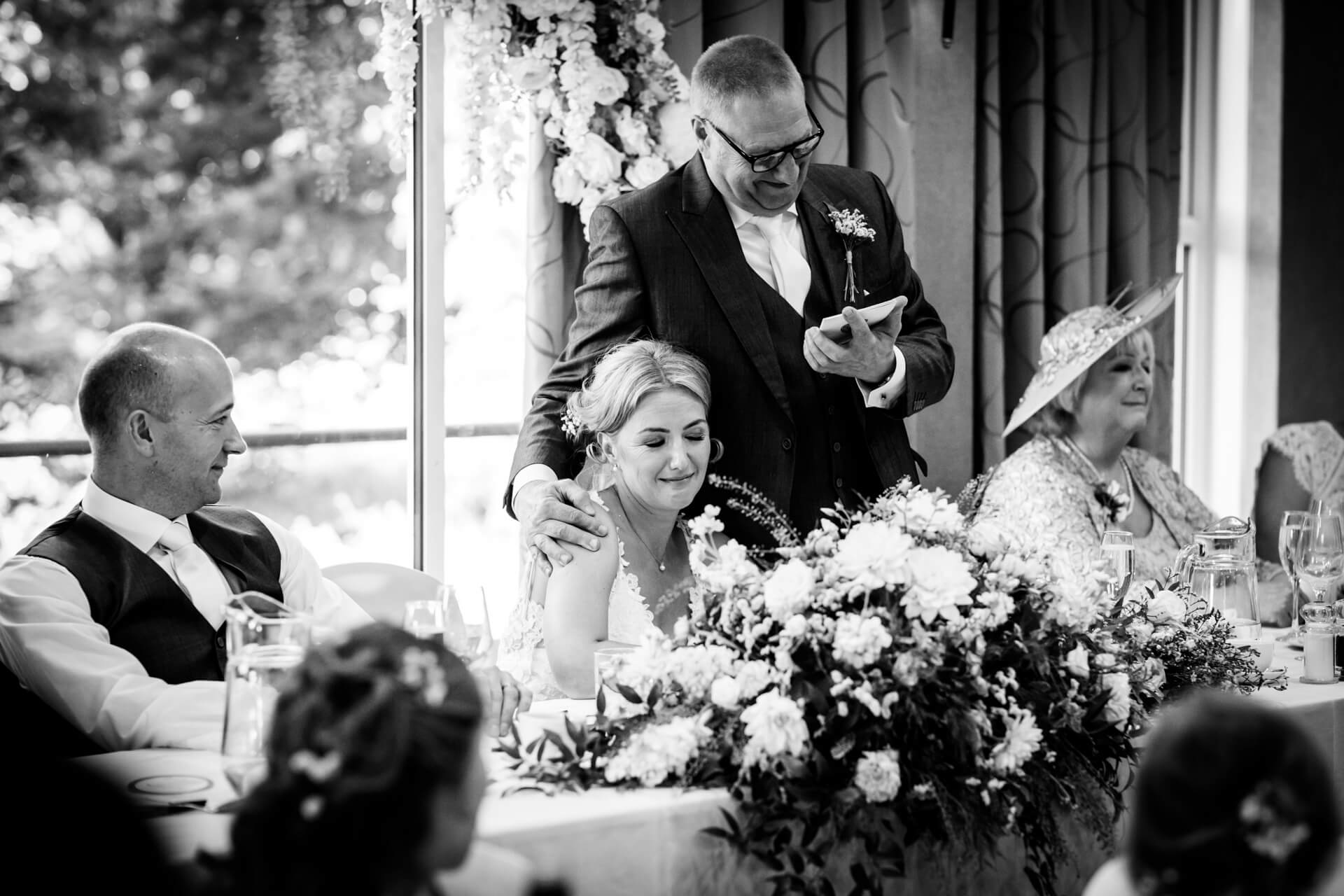 father of the bride putting his arm around the bride whilst making a speech