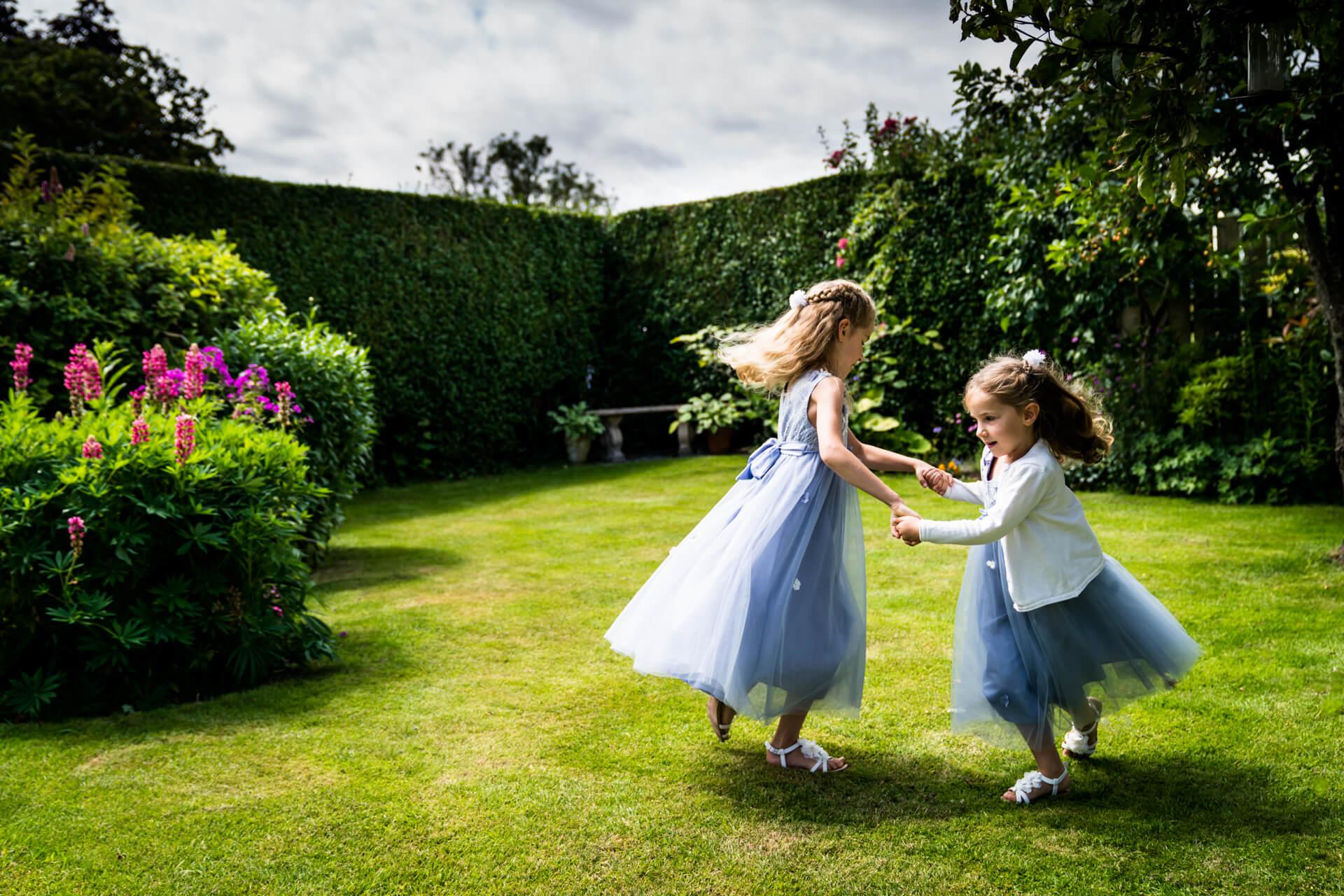 flower girls dancing together in a their garden
