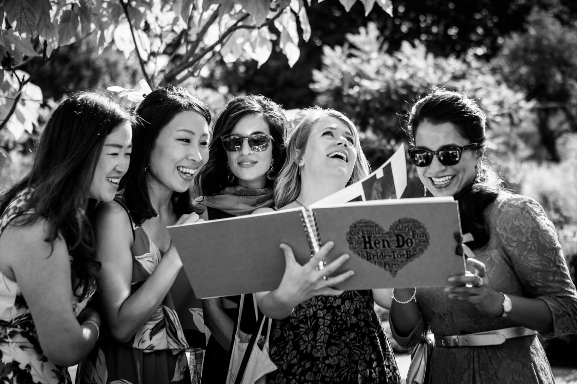 friends of the bride looking through an album of hen party photographs and laughing