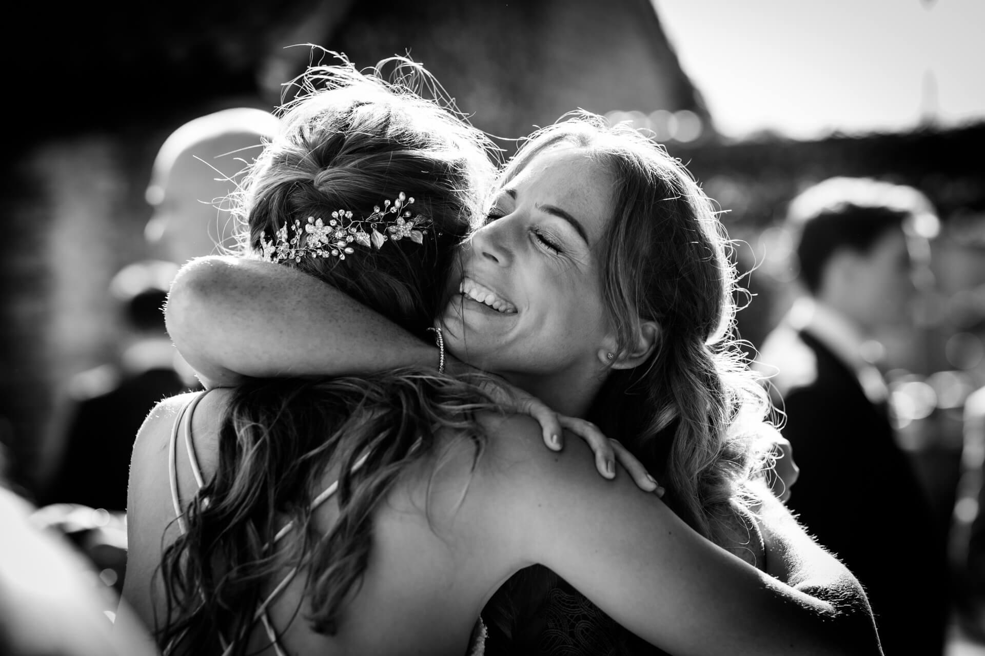 a wedding guest hugging the bride
