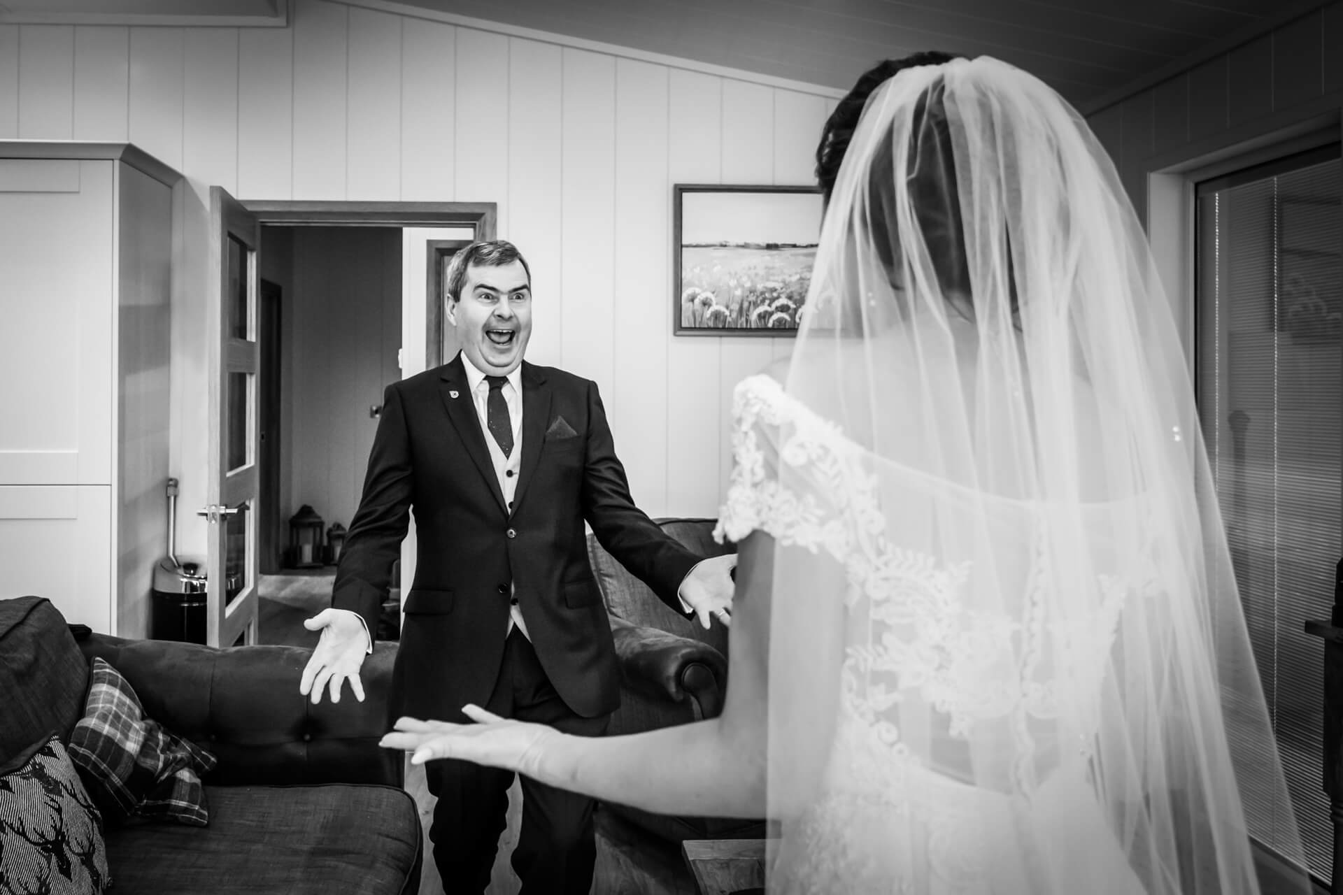 father of the bride laughing with delight on seeing the bride for the first time
