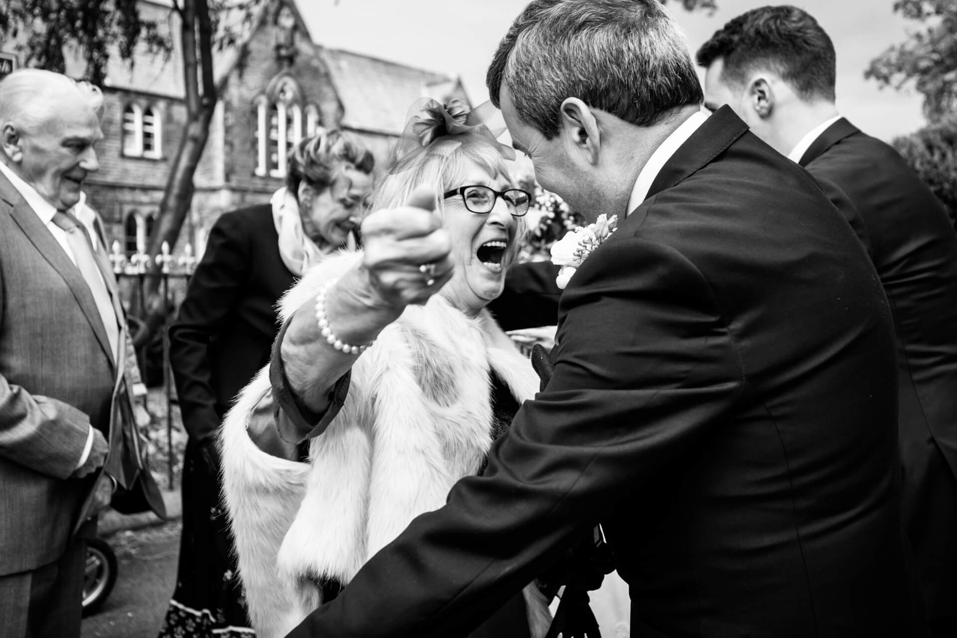 a guest smiling and hugging the father of the bride