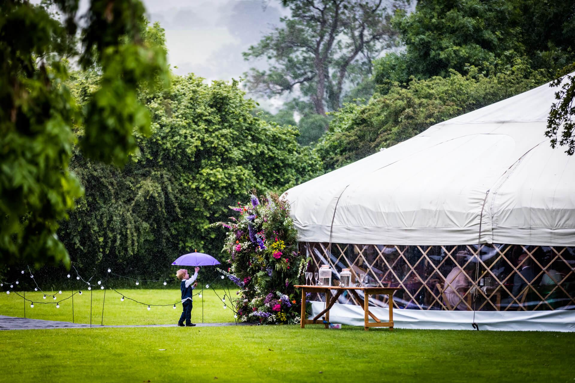 a pageboy holding an umbrella up outside a wedding yurt