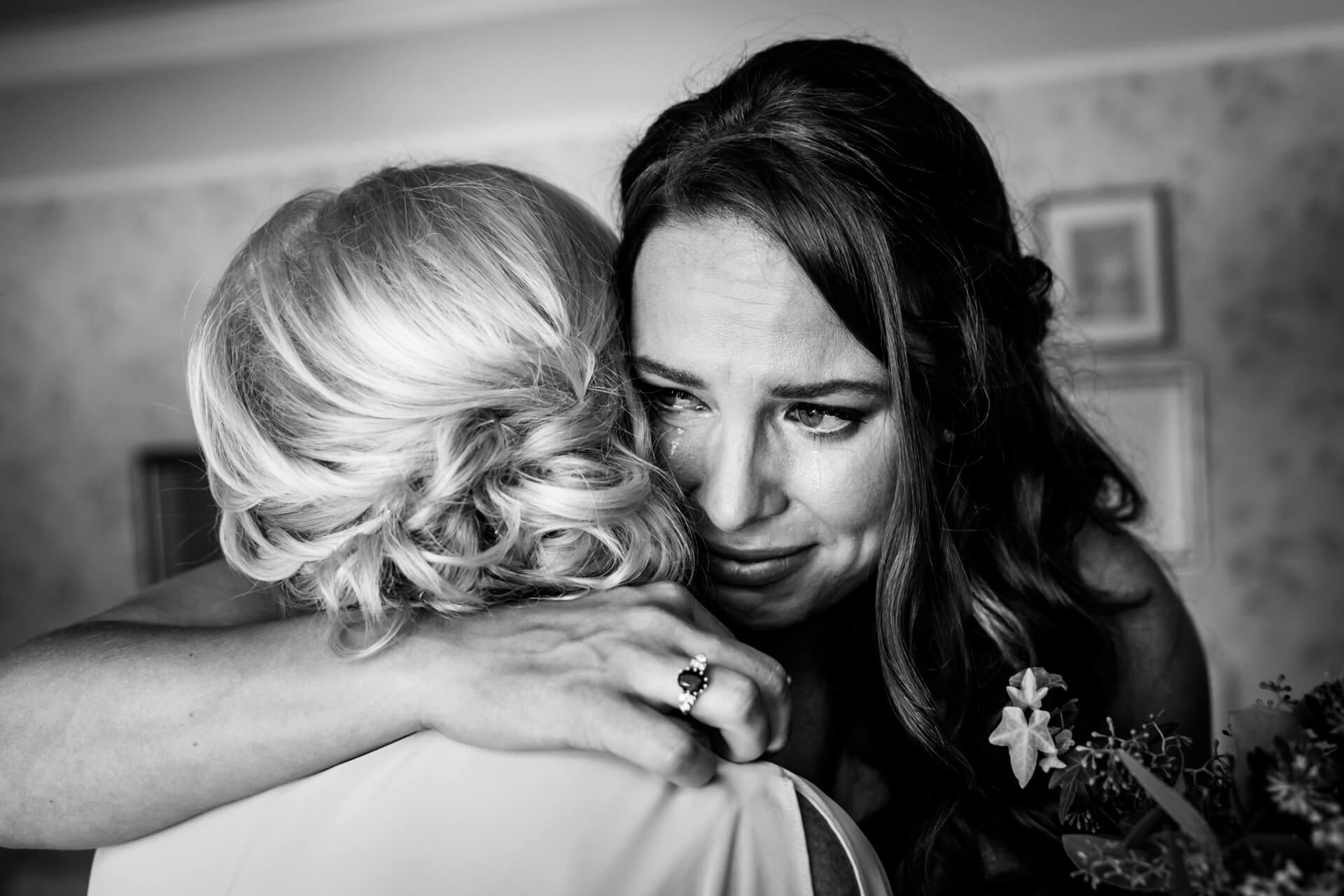 bride hugging her mother and shedding a tear