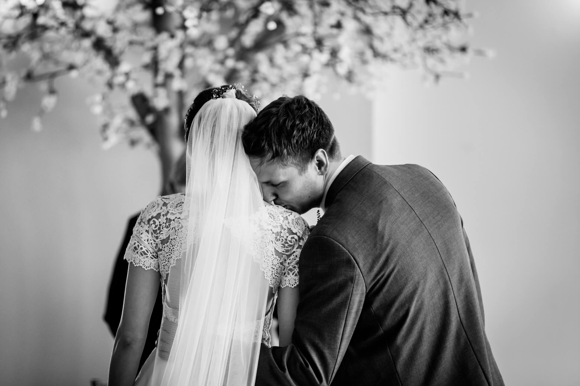 groom kissing his bride on the shoulder during the ceremony