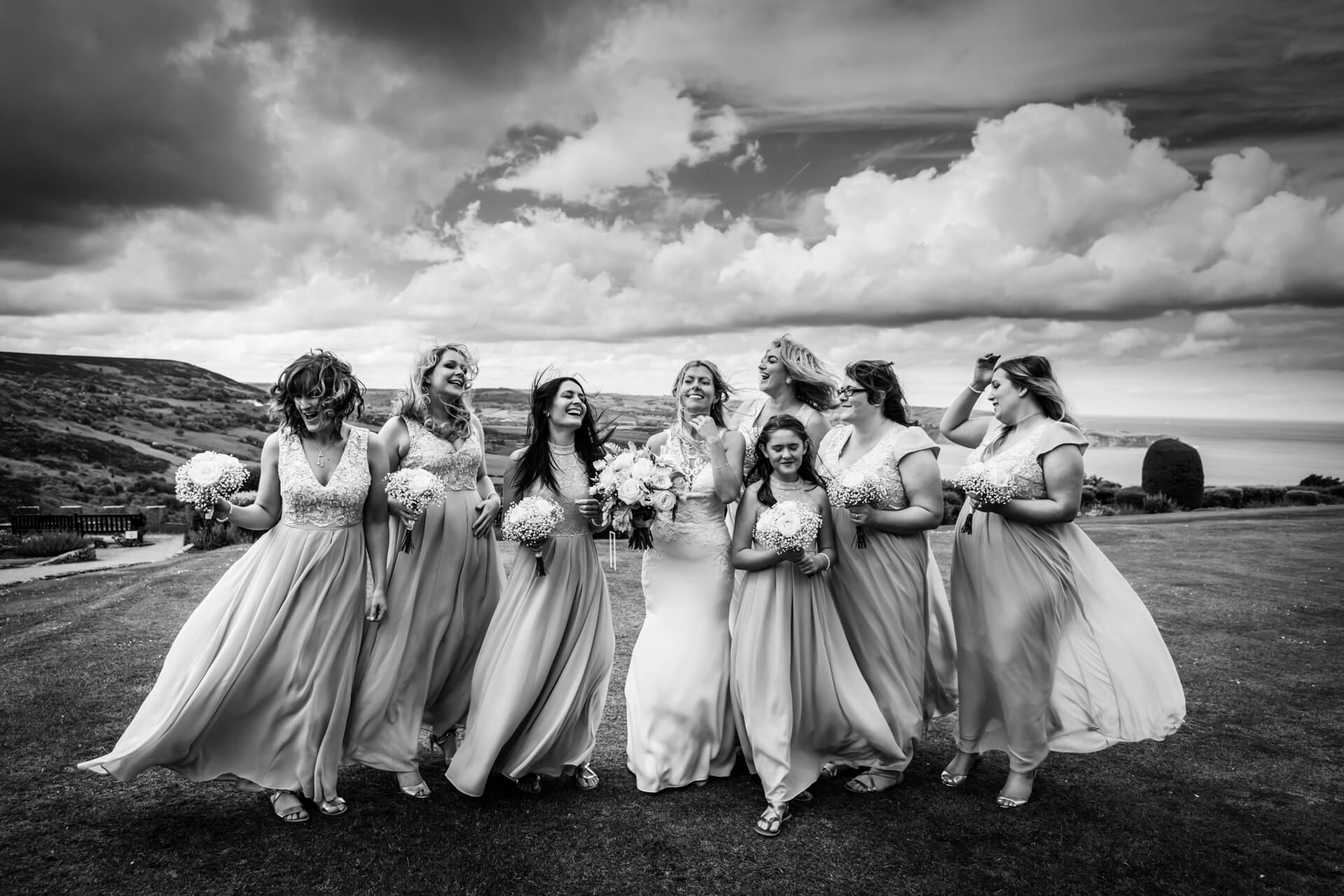 bride and bridesmaids standing on a windblown hill and laughing