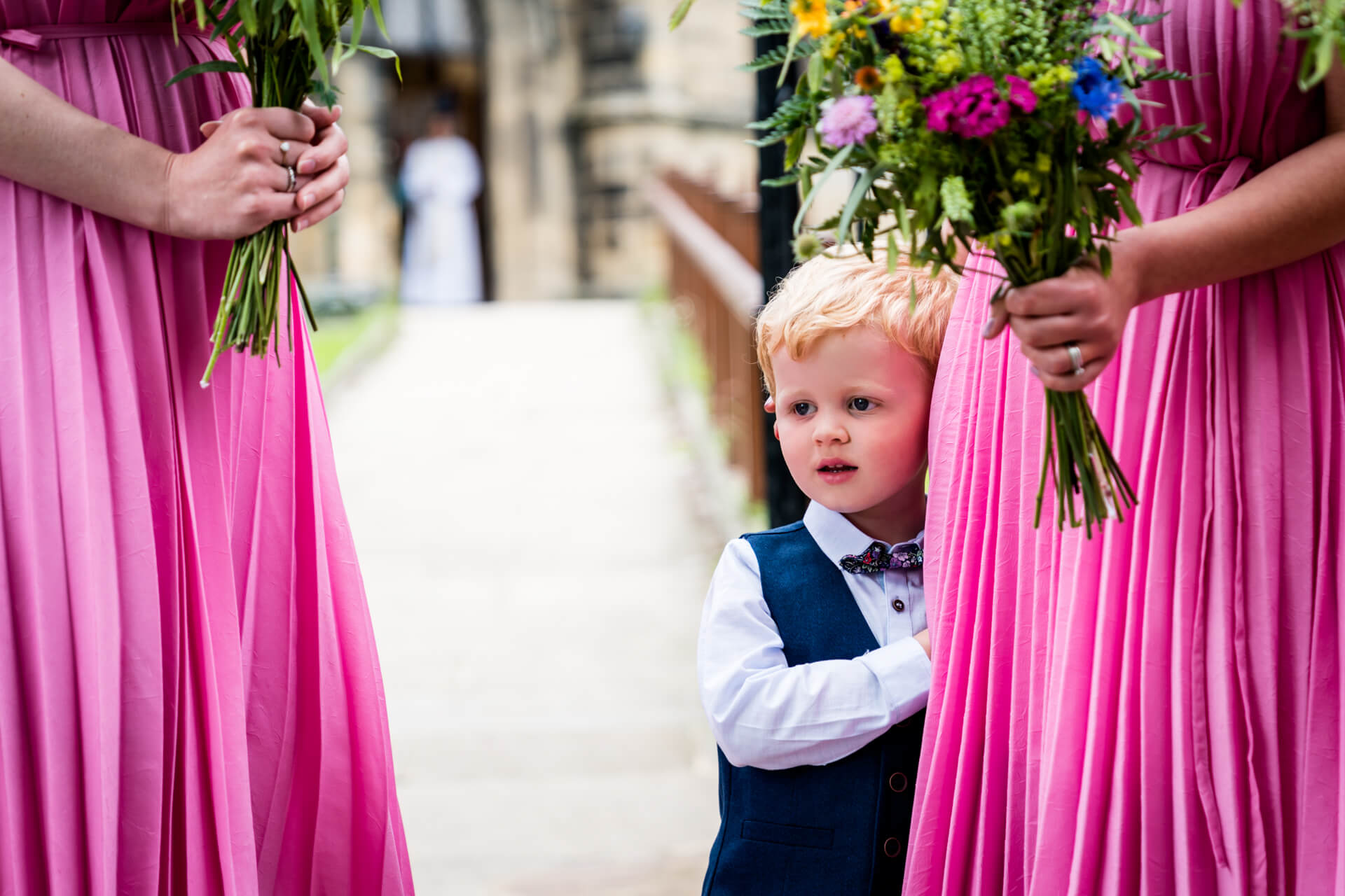 pageboy holding onto the skirt of a bridesmaid