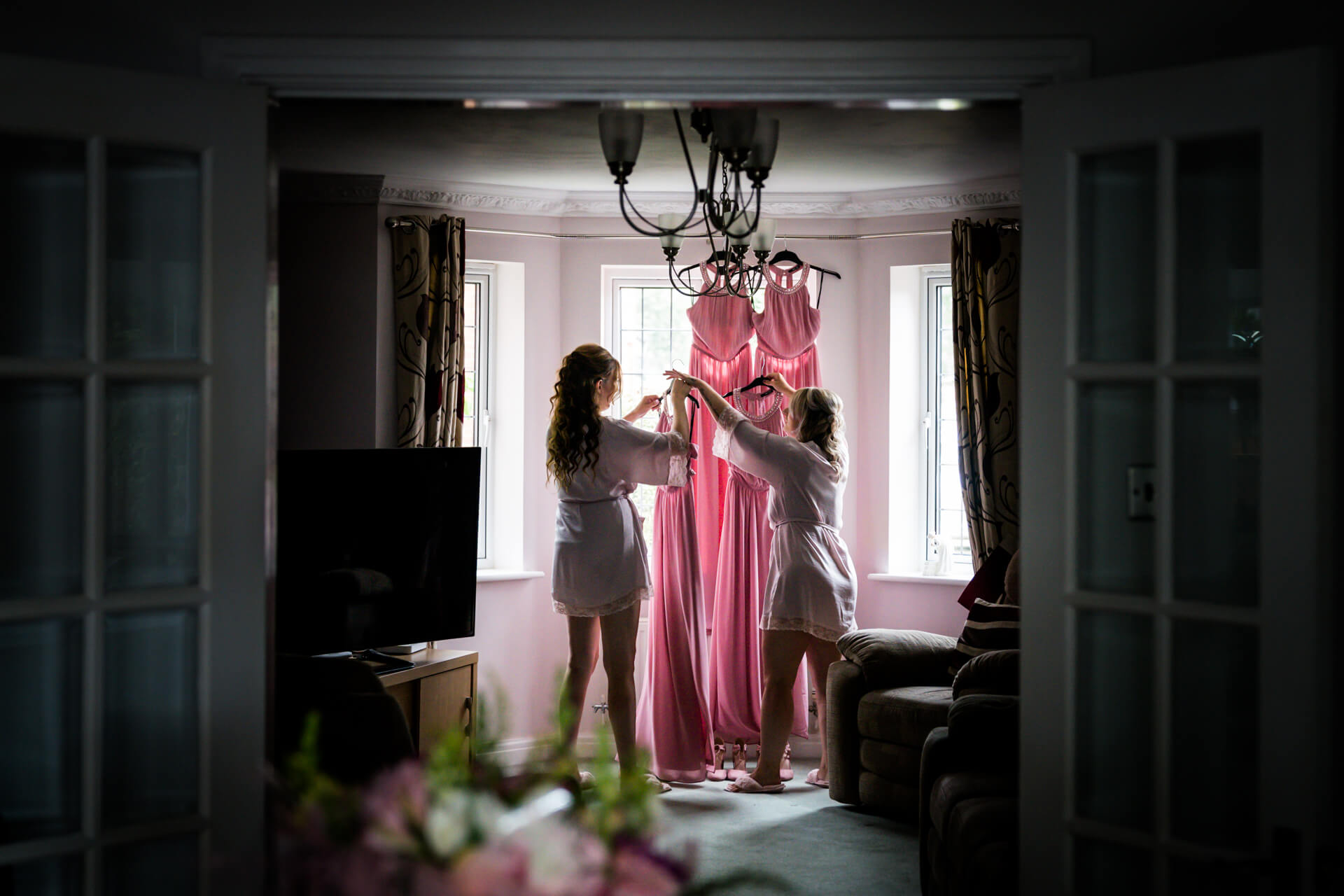 bridesmaids hanging the dresses in a window